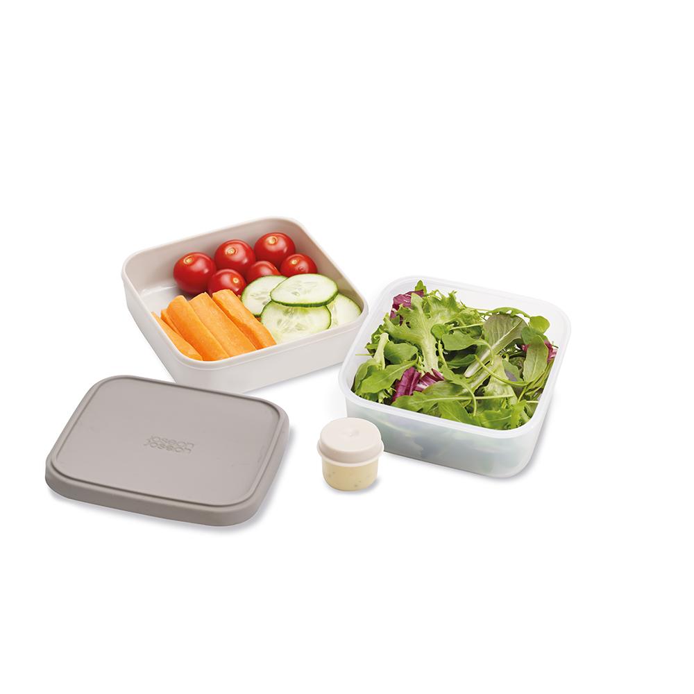 Ланч-бокс для салатов компактный GoEat серый. 8103081030Новая линейка универсальных контейнеров GoEat с отдельными ёмкостями для разных продуктов специально разработана для того, чтобы вы могли брать с собой в офис или на прогулку разные блюда для полноценного обеда. Компактный контейнер для салатов Space-saving salad box иделаьно подходит для салатов. В верхнюю ёмкость можно положить свежие листья и зелень, в нижнюю основную - другие ингредиенты (овощи, курицу, рыбу и т.д.). Для переноски соуса есть отдельная капсула. Все контейнеры имеют герметичную силиконовую крышку и надёжное блокирующее кольцо, что гарантирует сохранность продуктов и обезопасит от протекания. Когда контейнеры пустые, они легко складываются друг в друга для удобной переноски. Верхняя ёмкость - 400 мл Нижняя ёмкость - 700 мл Капсула для соуса - 20 мл Можно мыть в посудомоечной машине. Контейнеры можно разогревать в микроволновой печи, предварительно удалив кольцо и крышку.