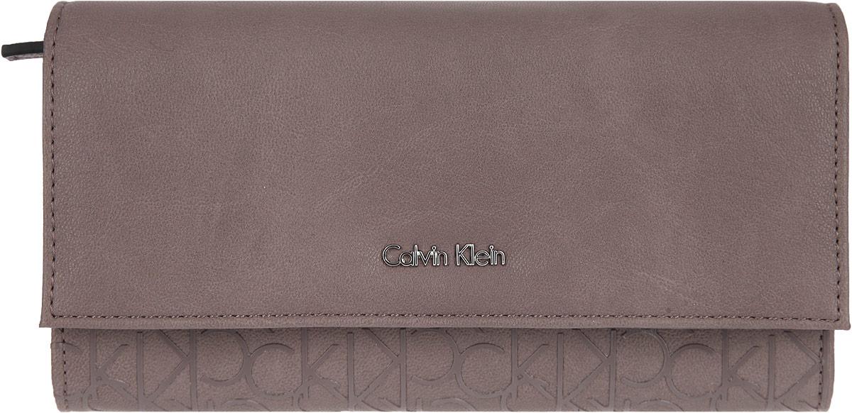 Кошелек женский Calvin Klein Jeans, цвет: тауп. K60K600606K60K600606Стильный кошелек Calvin Klein Jeans изготовлен из искусственной кожи. Закрывается изделие на клапан с кнопкой. Внутри содержатся два отделения для купюр, отделение для мелочи на застежке-молнии, карман для документов, потайной карман и десять кармашков для визиток и пластиковых карт. Кошелек упакован в фирменную коробку. Такой кошелек станет замечательным подарком человеку, ценящему качественные и практичные вещи.