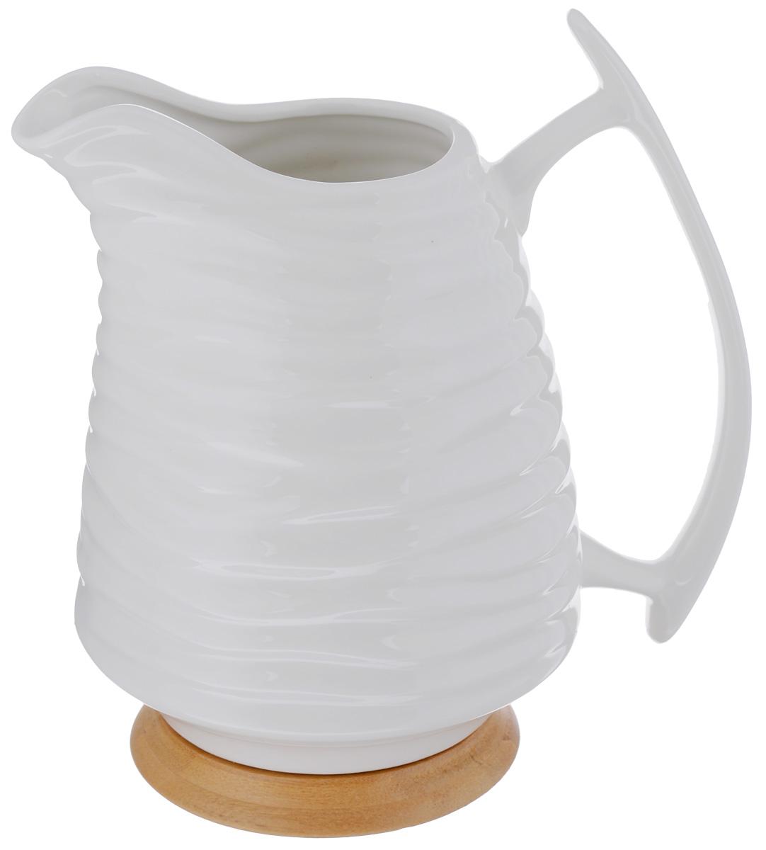 Кувшин Elan Gallery Айсберг, на подставке, 1,7 л540076Кувшин Elan Gallery Айсберг, выполненный из высококачественной керамики, оснащен эргономичной ручкой. Деревянная подставка предотвратит повреждение поверхности стола. Внешние стенки изделия декорированы рельефным рисунком. В таком кувшине будет удобно хранить и подавать на стол молоко, соки или воду. Кувшин Elan Gallery Айсберг украсит любой кухонный интерьер и станет хорошим подарком для ваших близких. Размер (по верхнему краю): 12 х 7,5 см. Высота (с учетом подставки): 22 см.