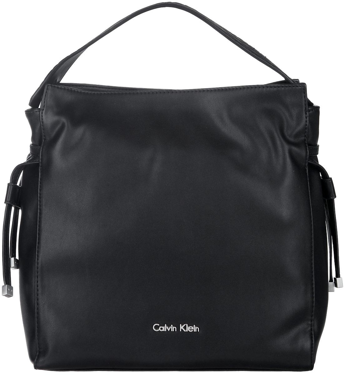 Сумка женская Calvin Klein, цвет: черный. K60K601026K60K601026Стильная женская сумка Calvin Klein выполнена из полиуретана, оформлена металлической фурнитурой с символикой бренда. Изделие содержит одно вместительное отделение и закрывается на магниты. Внутри расположены два накладных кармана и врезной карман на молнии. Сумка оснащена широкой лямкой для переноски и съемным плечевым ремнем. Оригинальный аксессуар от Calvin Klein позволит вам завершить образ и быть неотразимой.