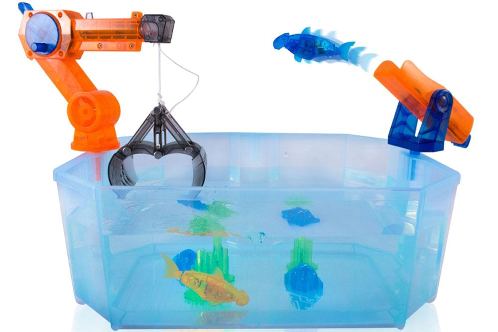 HexBug Робот AquaBot Harbour460-3359В наборе Aquabot Harbour входит микроробот рыбка Aquabot, специальный аквариум для него, элементы ландшафта, кран и катапульта! Микроробот Aquabot плавает как настоящая рыба и непредсказуем в направлении движения. Опустите его в воду и он оживет! Вне воды микроробот автоматически выключается. Запустите микроробота с помощью катапульты и постарайтесь его поймать с помощью крана. Это сделать не так уж и просто. Вас ожидают часы увлекательной игры с этим набором. Используя этот набор вам не придется ухаживать и чистить аквариум как за настоящими рыбками. Все что вам нужно, это только налить воды и опустить микроробота в аквариум.
