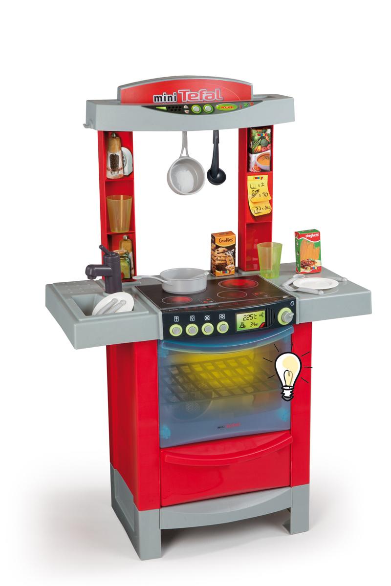 Smoby Игровой набор Кухня Mini Tefal цвет красный24147Если ваш ребенок любит помогать маме на кухне, играть с посудой, варить и жарить, но вам приходится ограничивать его в игре с бьющимися предметами кухонной утвари, то эта детская кухня создана специально для юного поваренка. Игровой набор Smoby Кухня Mini Tefal - красивая и очень реалистичная кухня со звуковыми и световыми эффектами для юных хозяек от трех лет. Эта компактная кухня со многими электронными функциями. Благодаря своим эргономичным размерам, она нуждается в минимальном пространстве для размещения в детской. Все как в настоящей кухне - мойка с краном, духовой шкаф с подсветкой, варочная панель, имитирующая звуки приготовления пищи. В набор входят аксессуары для игры: сотейник, поварешка, кружка, два стакана, тарелки, ложки, вилки, нож и продукты. С такой кухней ваш ребенок сможет устроить для своих игрушек удивительный обед. Порадуйте его таким замечательным подарком! Игра с с набором развивает фантазию, а набор хозяйственных предметов оптимален для...