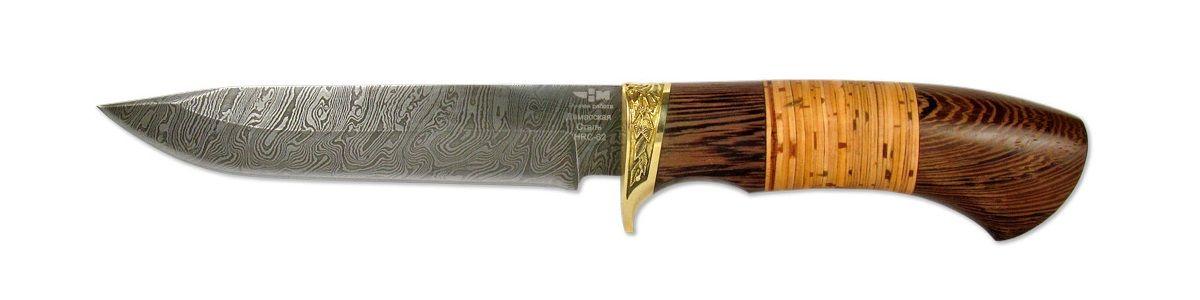 Нож охотничий Ножемир Клен, 14,7 смКЛЁН (2154)дНож из дамасской стали КЛЁН (2154)д производится Компанией Ножемир. Дамасская сталь получается при многократной перековке стального пакета, который состоит из сталей с различным содержанием углерода. Для того чтобы узор проявился на клинке применяется особая технология, в основе которой лежит высоколегированная сталь, армированная наиболее упругими волокнами. У клинка толщина толщину 2,4 мм и закалка до твердости 58-62 HRC. Нож прекрасно сбалансирован и управляем. Удобен для разных сфер применения, хоть лося разделать или колбаску нашинковать - хороший дамасский нож справится со всеми этими задачами без проблем. Но есть один недостаток ножей из дамасской стали - дамаск подвержен коррозии, и требует к себе особого внимания. Нож КЛЁН (2154)д - обладает оптимальными характеристиками с хорошей износоустойчивостью и твердостью. Рукоятка ножа, созжанная из ценных пород древесины, может быть украшена декоративными вставками и художественным литьём из мельхиора, латуни или других сплавов.