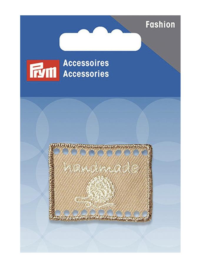Эмблема Prym Handmade, цвет: бежевый, 4 х 3 см7710983Эмблемы предназначены для пришивания, а также использования в качестве дизайнерских ярлычков на одежде, сумках, рюкзаках, шапках и так далее.