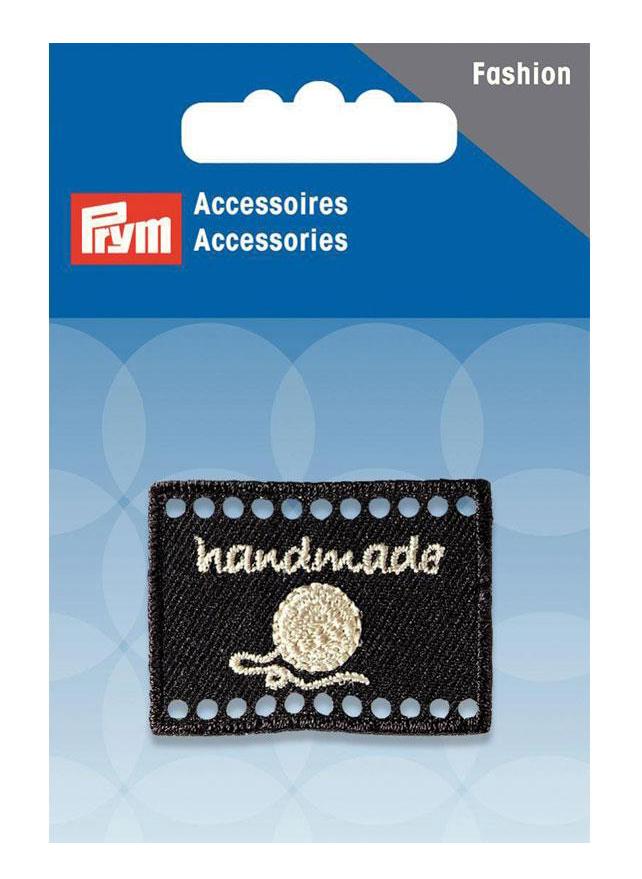 Эмблема Prym Handmade, цвет: черный, 4 х 3 см7710985Эмблемы предназначены для пришивания, а также использования в качестве дизайнерских ярлычков на одежде, сумках, рюкзаках, шапках и так далее.