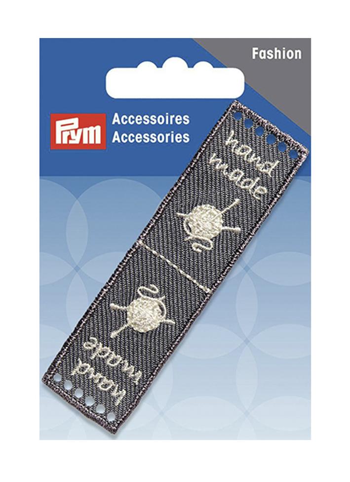 Эмблема Prym Handmade, цвет: серый, 8 х 2 см7710987Эмблемы предназначены для пришивания, а также использования в качестве дизайнерских ярлычков на одежде, сумках, рюкзаках, шапках и так далее.