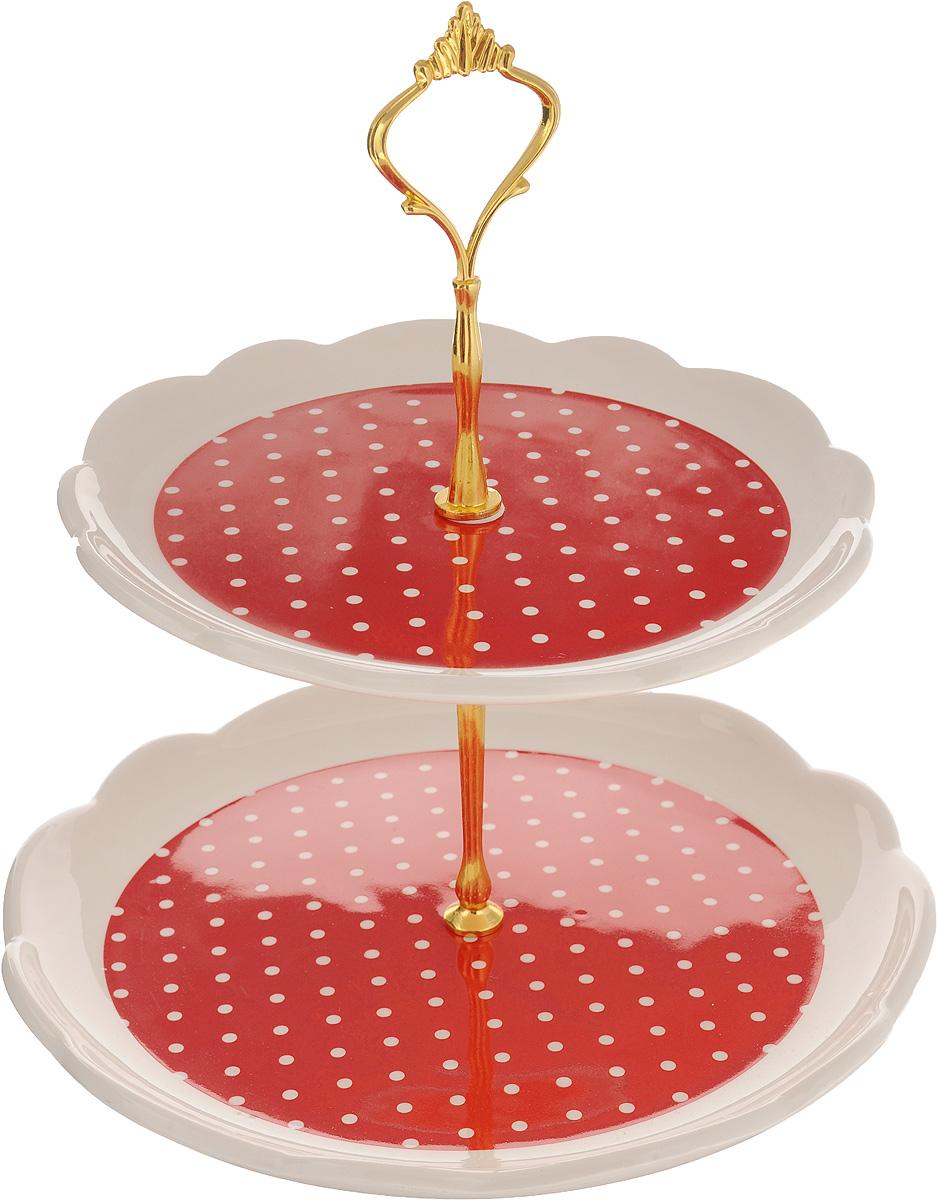 Фруктовница Loraine, 2-ярусная. 2586525865Фруктовница Loraine, выполненная из высококачественной керамики, сочетает в себе классический дизайн с максимальной функциональностью. Изделие состоит из 2 блюд разного диаметра, которые имеют волнистые края и оформлены в красно-белых тонах с принтом в горошек. Стойка-держатель выполнена из металла с золотистым напылением. Фруктовница предназначена для красивой сервировки конфет, фруктов и десертов. Элегантная и стильная, она украсит сервировку вашего стола и подчеркнет прекрасный вкус хозяйки, а также станет отличным подарком. Подходит для использования в холодильнике и посудомоечной машине. Блюда можно ставить в СВЧ. Диаметр блюд: 20,5 см; 24,5 см. Высота фруктовницы: 28 см.