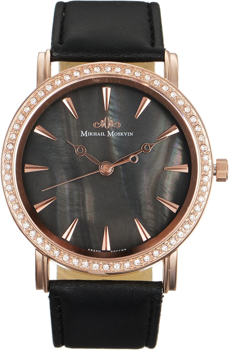 Часы наручные женские Mikhail Moskvin Каприз, цвет: черный, золотой. 586-8-4586-8-4Стильные женские наручные часы Mikhail Moskvin Каприз изготовлены из высокотехнологичной гипоаллергенной нержавеющей стали и дополнены ремешком из искусственной кожи, охватываемый двойными элегантными ушами. Для того чтобы защитить циферблат от повреждений в часах используется высокопрочное минеральное стекло. Модель выпускается с высокоточным японским кварцевым механизмом, производства фирмы Seiko Epson, который оснащен часовой, минутной и секундной стрелками. Корпус традиционной формы, рант которого украшают сверкающие стразы. Часы и минуты отображаются с помощью объемных золотистых знаков и стрелок в стиле Бреге на поле циферблата из темного перламутра. Браслет комплектуется надежной и удобной в использовании застежкой-пряжкой, которая позволит с легкостью снимать и надевать часы, а также регулировать длину браслета. Часы упакованы в блистер. Часы Mikhail Moskvin для современных и стильных людей, которые стремятся выделиться из толпы и подчеркнуть свою...