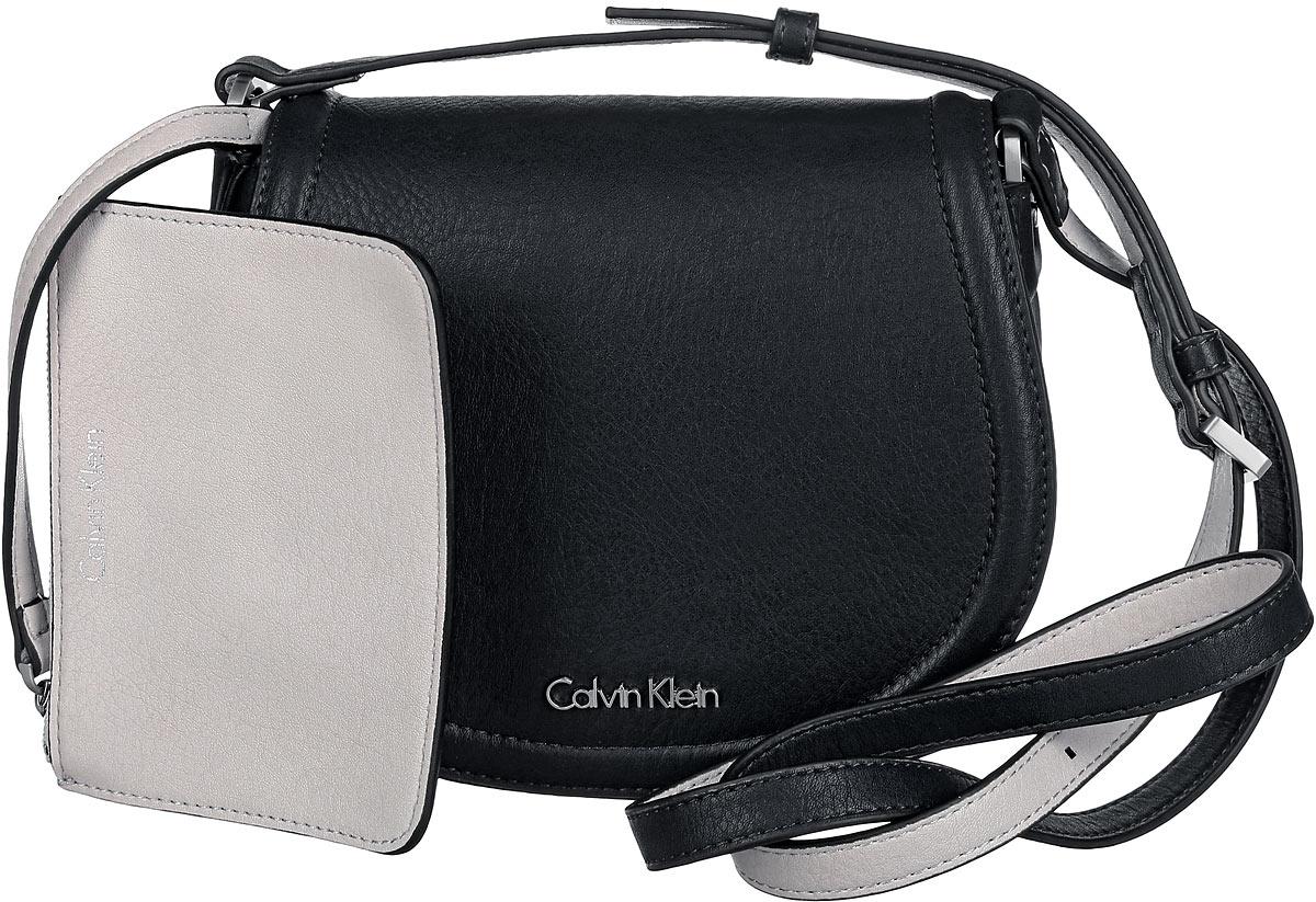 Сумка женская Calvin Klein Jeans, цвет: черный. K60K601646_9100K60K601646_9100Стильная сумка Calvin Klein выполнена из искусственной кожи с зернистой фактурой, оформлена металлической фурнитурой с логотипом бренда. Изделие содержит одно отделение, которое закрывается клапаном на магнитную кнопку. Внутри сумки размещены накладной кармашек для мелочей и врезной карман на застежке-молнии. Сумка оснащена практичным плечевым ремнем регулируемой длины. В комплекте с изделием поставляется небольшой кошелек на застежке-молнии, который фиксируется к сумке при помощи карабина, и чехол для хранения. Модная сумка идеально подчеркнет ваш неповторимый стиль.