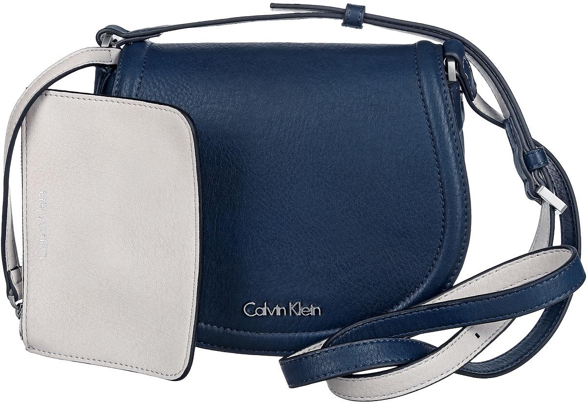 Сумка женская Calvin Klein Jeans, цвет: темно-синий. K60K601646_9020K60K601646_9020Стильная сумка Calvin Klein выполнена из искусственной кожи с зернистой фактурой, оформлена металлической фурнитурой с логотипом бренда. Изделие содержит одно отделение, которое закрывается клапаном на магнитную кнопку. Внутри сумки размещены накладной кармашек для мелочей и врезной карман на застежке-молнии. Сумка оснащена практичным плечевым ремнем регулируемой длины. В комплекте с изделием поставляется небольшой кошелек на застежке-молнии, который фиксируется к сумке при помощи карабина, и чехол для хранения. Модная сумка идеально подчеркнет ваш неповторимый стиль.