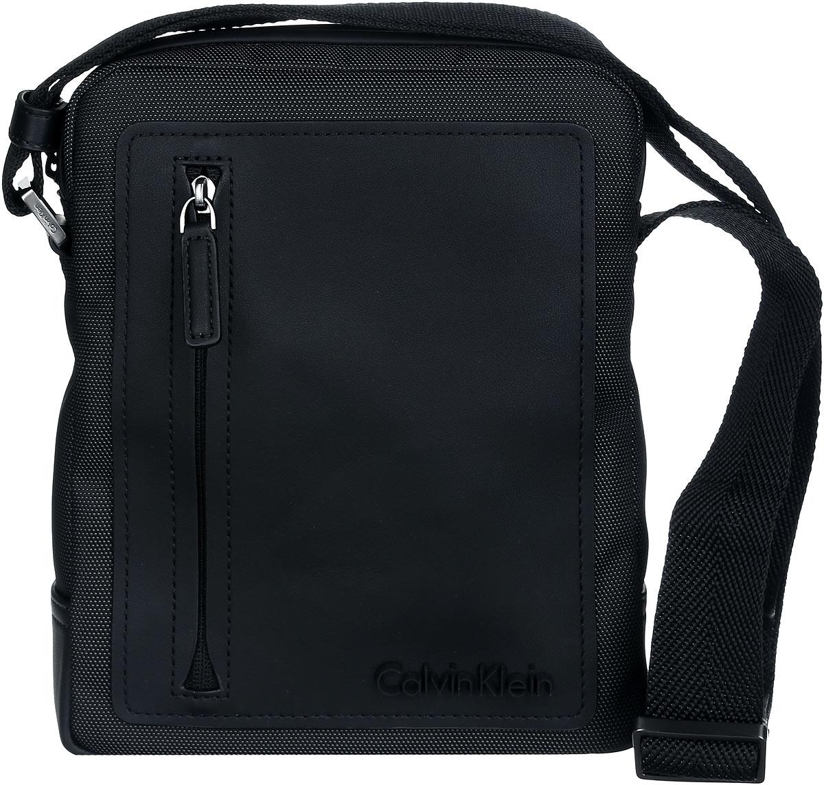 Сумка мужская Calvin Klein Jeans, цвет: черный. K50K501618_0010K50K501618_0010Стильная сумка Calvin Klein выполнена из полиуретана, оформлена символикой бренда. Изделие содержит одно отделение, которое закрывается на застежку-молнию. Внутри сумки размещены два накладных кармашка для мелочей и врезной карман на застежке-молнии. Сумка оснащена плечевым ремнем регулируемой длины. Лицевая сторона дополнена накладным карманом на молнии. В комплекте с изделием поставляется чехол для хранения. Модная сумка идеально подчеркнет ваш неповторимый стиль.