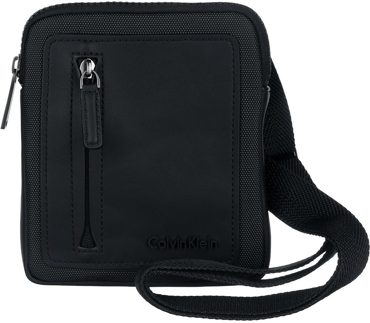 Сумка мужская Calvin Klein Jeans, цвет: черный. K50K501607_0010K50K501607_0010Стильная сумка Calvin Klein выполнена из полиуретана и текстиля, оформлена символикой бренда. Изделие содержит одно отделение, которое закрывается на застежку-молнию. Внутри сумки размещены накладной кармашек для мелочей и врезной карман на застежке-молнии. Сумка оснащена плечевым ремнем регулируемой длины. Лицевая сторона дополнена накладным карманом на молнии. В комплекте с изделием поставляется чехол для хранения. Модная сумка идеально подчеркнет ваш неповторимый стиль.