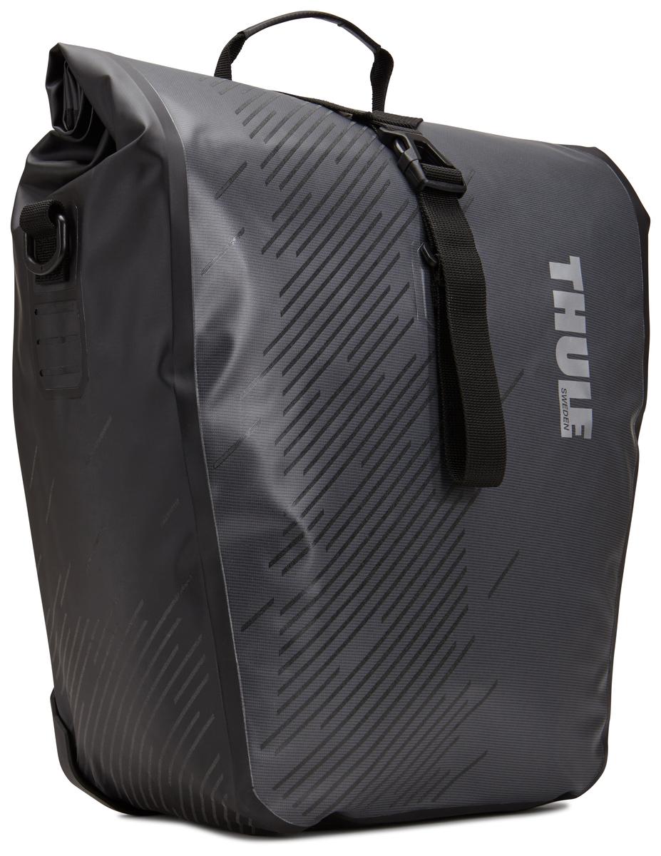 Набор велосипедных сумок Thule Pack?n Pedal Shield Pannier, цвет: темно серый, 2 шт. Размер L100061Эти многофункциональные водонепроницаемые сумки обеспечивают безопасность и защиту благодаря ярким светоотражающим элементам и сворачивающейся верхней части. Единая конструкция со сворачивающейся верхней частью гарантирует, что вещи внутри останутся сухими и чистыми. Система крепления на магнитах проста в использовании, надежна и имеет малый уровень вибрации. Яркие светоотражающие элементы на передней и боковой панелях улучшают заметность на дороге. Удобные точки крепления для фонарей обеспечивают дополнительную безопасность. Внутренние карманы для хранения мелких вещей. Встроенные ручки и отстегиваемый ремень для ношения через плечо обеспечивают несколько вариантов переноски. Лучше всего подходит для багажников Thule, но может использоваться практически с любым велосипедным багажником. Продаются парами.
