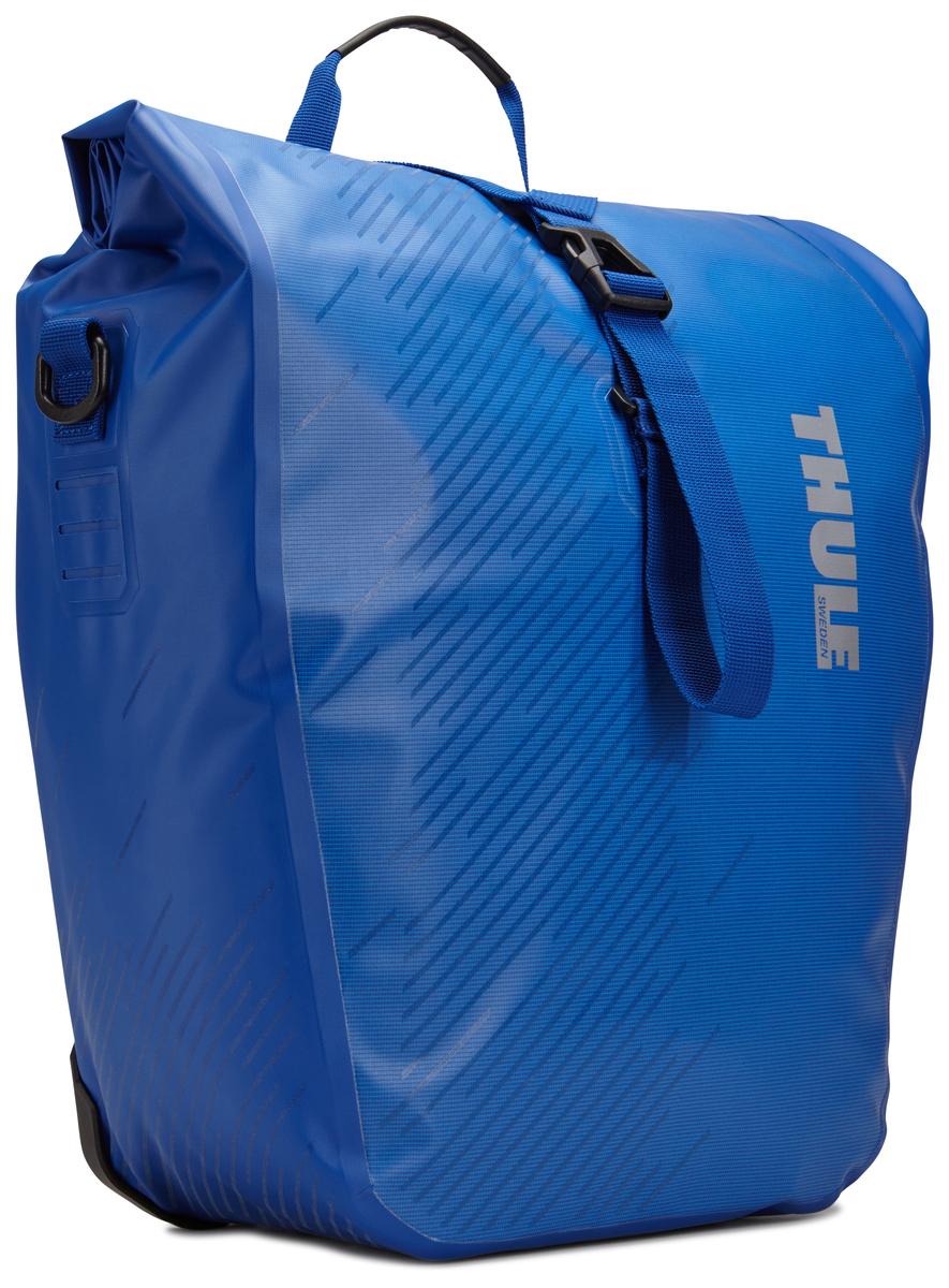 Набор велосипедных сумок Thule Shield, цвет: синий, 48 л, 2 шт100062Многофункциональные водонепроницаемые сумки Thule Shield обеспечивают безопасность и защиту благодаря ярким светоотражающим элементам. Единая конструкция со сворачивающейся верхней частью гарантирует, что вещи внутри останутся сухими и чистыми. Система крепления на магнитах проста в использовании, надежна и имеет малый уровень вибрации. Яркие светоотражающие элементы на передней и боковой панелях улучшают заметность на дороге. Удобные точки крепления для фонарей обеспечивают дополнительную безопасность. Имеются внутренние сетчатые карманы для хранения мелких вещей. Встроенные ручки и отстегиваемый ремень для ношения через плечо обеспечивают несколько вариантов переноски. Лучше всего подходит для багажников Thule, но может использоваться практически с любым велосипедным багажником. В набор входят две сумки объемом 48 л.