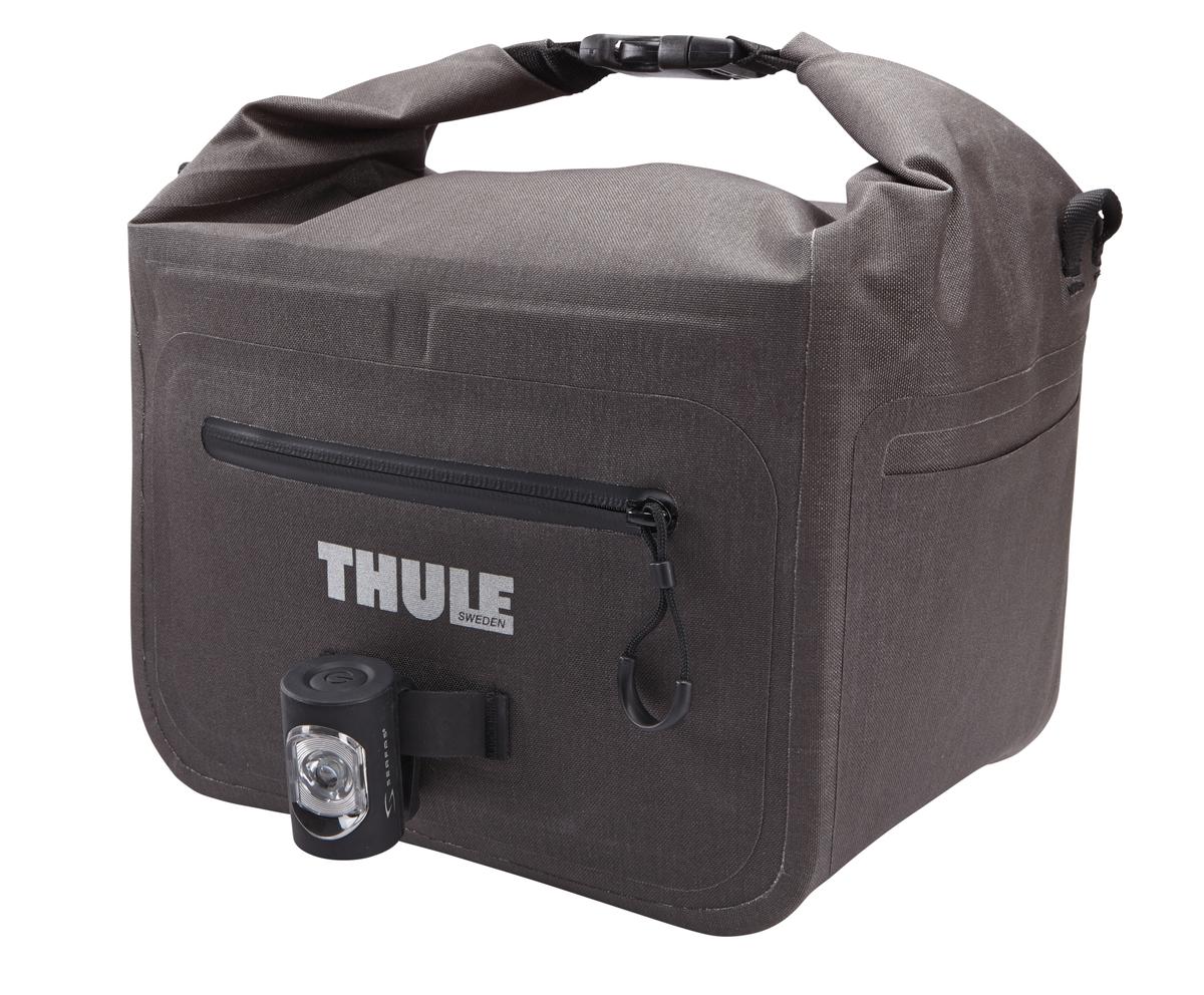 Сумочка для мелочей на руль Thule Базовая, цвет: черный100080Эта компактная, водонепроницаемая 9-литровая сумка позволяет велосипедистам хранить важные вещи под рукой. Водонепроницаемая сворачивающаяся/разворачивающаяся верхняя часть помогает сохранить вещи сухими. Вшитая петля обеспечивает крепление аварийного фонаря на переднюю часть сумки. Светоотражающие полоски повышают заметность на дороге. Сворачивающаяся застежка может также служить удобной ручкой для переноски.