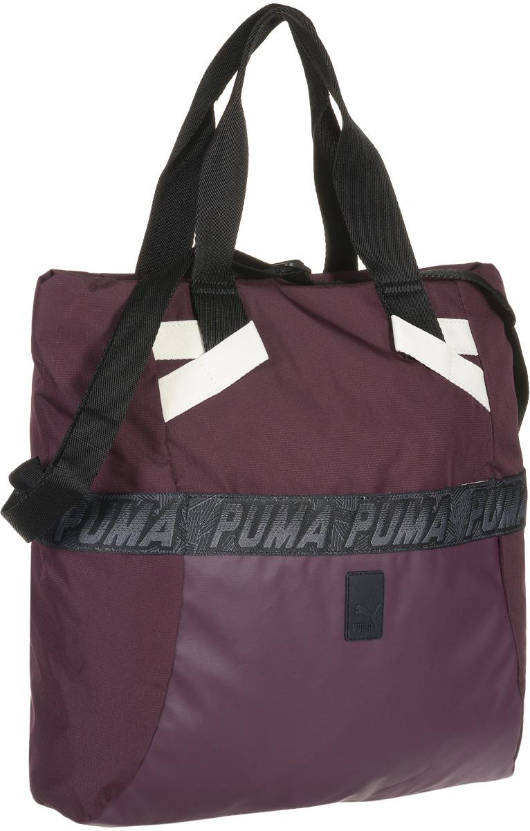 Сумка женская Puma Evo Plus Shopper W, цвет: темно-пурпурный. 0742160107421601Вместительная сумка Evo Plus Shopper W от Puma выполнена из полиэстера с водоотталкивающим покрытием, декорирована фирменными надписями на передней и боковых панелях сумки, резиновой нашивкой с логотипом Puma Cat спереди. Сумка имеет главное отделение на молнии, открывающейся с двух сторон, накладной карман спереди и прорезной карман на молнии внутри. Функциональная подкладка из полиэстера, водоотталкивающее покрытие нижней части обеспечивают максимум удобства. Сумка очень эргономична, поэтому вы сможете разместить в ней все необходимое для тренировки или прогулок по городу. Основанный в 1948 году бренд Puma стал выбором многих героев мирового спорта. Дизайн Puma сосредоточен на стиле и функциональности моделей, поэтому коллекции брендовой одежды и обуви сочетают современный стиль с инновационными спортивными технологиями.