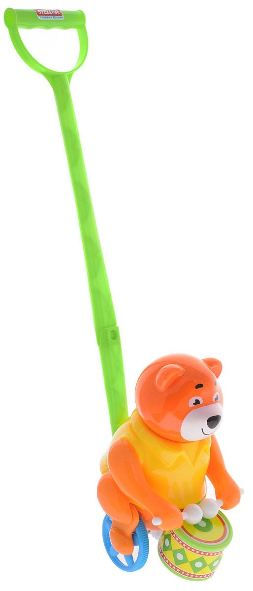 Stellar Игрушка-каталка Барабанщик цвет оранжевый желтый1377Игрушка-каталка Stellar Барабанщик - симпатичный мишка, который умеет стучать палочками по барабану. Мишка приветливо улыбается, поэтому на его мордочке всегда доброе выражение. Мишка-барабанщик станет хорошим другом для ребенка на прогулке и дома. Дети будут увлеченно бегать, держась за ручку каталки. Чем быстрее будет бегать ваш малыш, тем активнее мишка будет настукивать свои ритмы и сучить толстыми ножками. Такой забавный барабанщик обязательно понравится всем и подарит замечательное настроение вашим непоседам! Каталка развивает цветовое восприятие, координацию движений, звуко-моторную координацию. Формирует эмоциональную отзывчивость и игровые навыки.