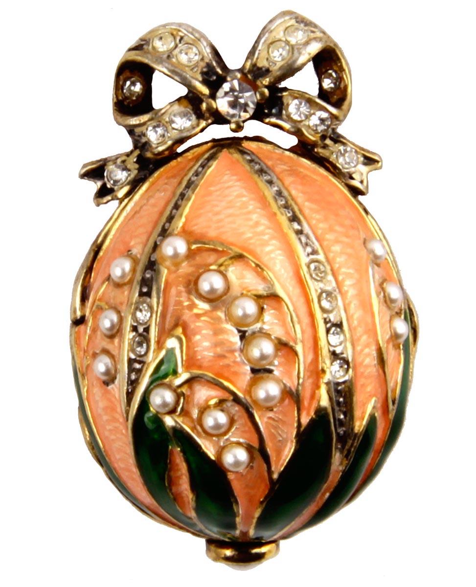 Кулон с часами Ландыши. Металл, эмаль, жемчуг, австрийские кристаллы, House of Faberge. Конец XX векаPD0089Кулон с часами Ландыши. Металл, эмаль, жемчуг, австрийские кристаллы. Западная Европа, Фаберже, конец XX века. Размер кулона 3 х 2 см, длина цепочки 48,5 см. Сохранность хорошая. Очень нежный кулон выполнен в виде яйца с изображением стеблей ландыша. Поверхность яйца покрыта розовой эмалью, цветы ландыша сделаны из белых искусственных жемчужин. Около петли для подвески помещен небольшой бант, украшенный прозрачными стразами. Внутри кулона помещены небольшие часики.