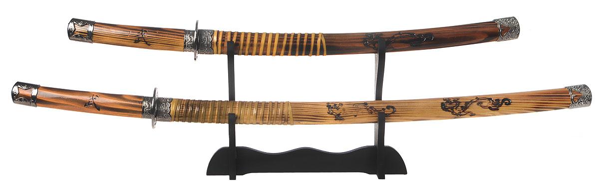 Набор самурайских мечей Русские Подарки, 2 предмета31154Набор самурайских мечей Русские Подарки станет чудесным подарком любителю восточной культуры. В комплект входит катана и вакидзаси. Клинки выполнены из высококачественной стали и защищены ножнами, изготовленными из дерева, украшенного рельефным рисунком и металлическими вставками. Рукоятки также выполнены из дерева, украшенного рельефным рисунком и металлическими вставками. Изделия устанавливаются на деревянную подставку. Такое сувенирное оружие станет изысканным подарком поклонникам культуры Востока и прекрасным дополнением интерьера вашей квартиры или офиса. Сувенирное оружие - это всегда блестящий подарок для мужчины, прекрасный вариант как для партнера по бизнесу, так и для любимого. Если вы заядлый коллекционер, то добавление нового декоративного оружия к своей коллекции будет ярким и приятным моментом в вашей жизни. Клинки не заточены. Длина катаны (с ножнами): 101 см. Длина клинка катаны: 70 см. Длина вакидзаси (с...
