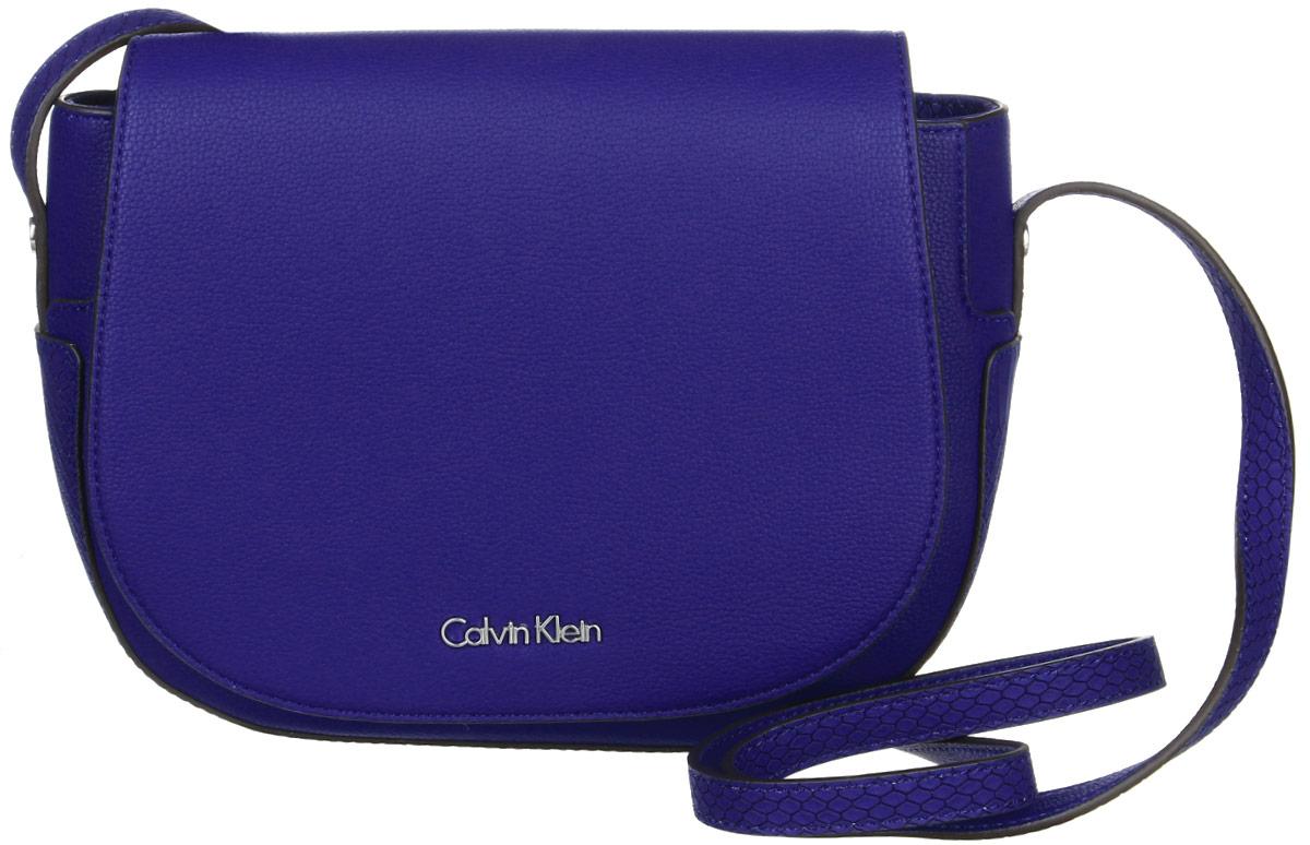 Сумка женская Calvin Klein Jeans, цвет: синий. K60K602332_433K60K602332_433Стильная сумка Calvin Klein Jeans выполнена из полиуретана. Изделие содержит одно большое отделение, которое закрывается на клапан и магнитный замок. Внутри сумки размещен один кармашек на застежке-молнии. Сумка оснащена плечевым ремнем регулируемой длины. Оформлена модель металлической пластиной с названием бренда. В комплекте с изделием поставляется чехол для хранения.