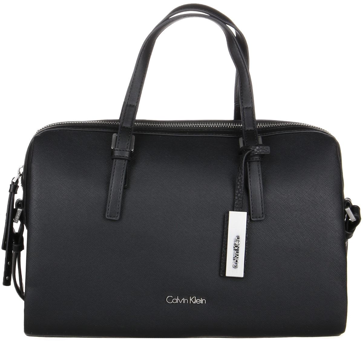 Сумка женская Calvin Klein Jeans, цвет: черный. K60K602160_001K60K602160_001Стильная сумка Calvin Klein Jeans выполнена из поливинилхлорида и полиуретана. Изделие содержит одно большое отделение, которое закрывается на застежку-молнию. Внутри сумки размещено два накладных кармашка для мелочей и один на застежке-молнии. Сумка оснащена плечевым ремнем регулируемой длины. Оформлена модель металлической пластиной с названием бренда и небольшим брелоком. В комплекте с изделием поставляется чехол для хранения.