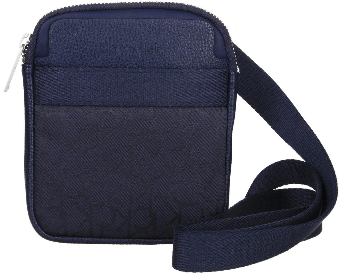 Сумка мужская Calvin Klein Jeans, цвет: темно-синий. K50K502138_000K50K502138_000Стильная сумка Calvin Klein Jeans выполнена из поливинилхлорида с добавлением хлопка и полиэстера, оформлена символикой бренда. Изделие содержит одно отделение, которое закрывается на застежку-молнию. Внутри сумки размещен один накладной кармашек для мелочей и один прорезной на застежке-молнии. Спереди расположен один открытый накладной карман. Сумка оснащена плечевым ремнем регулируемой длины. В комплекте с изделием поставляется чехол для хранения.