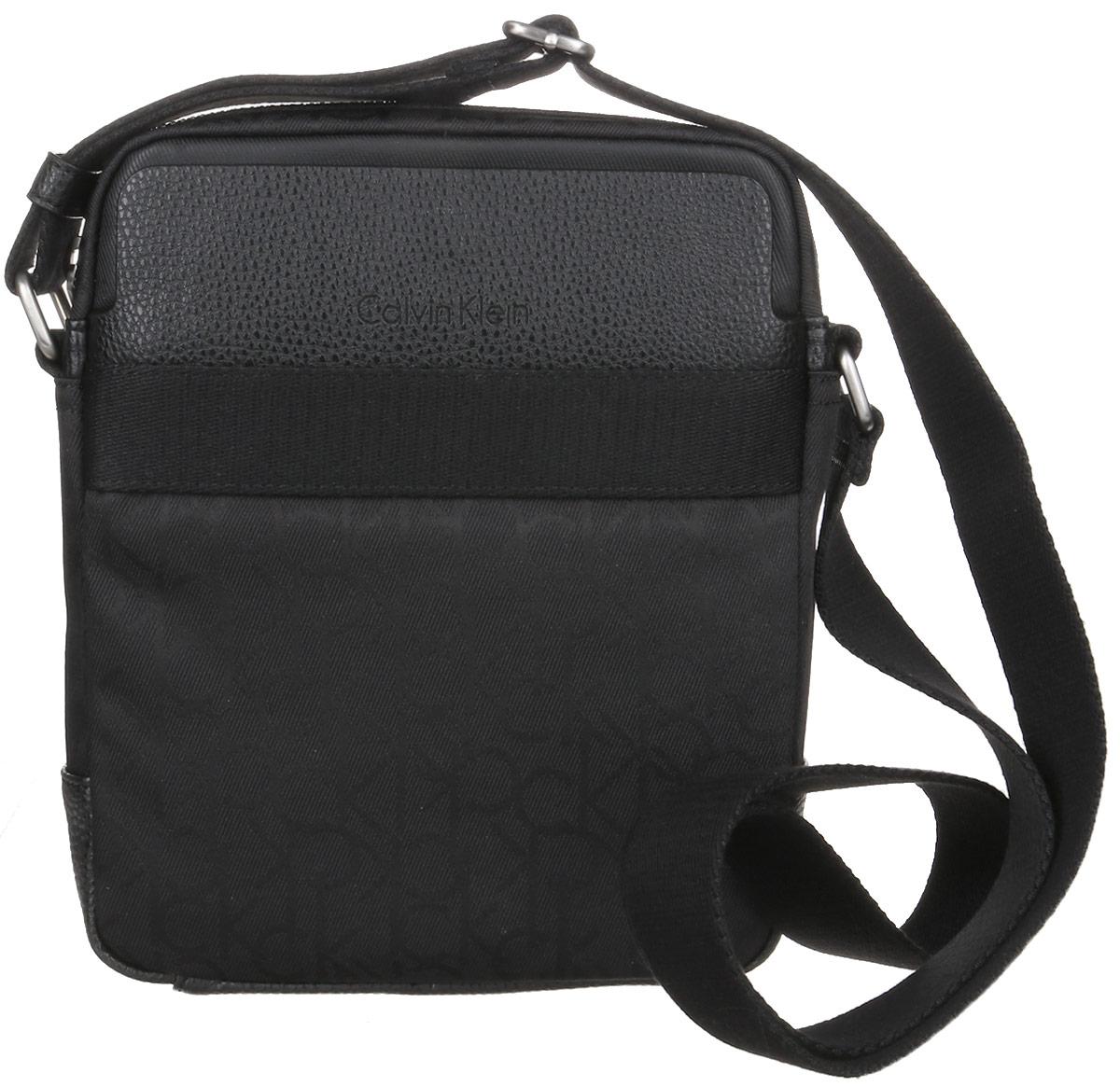 Сумка мужская Calvin Klein Jeans, цвет: черный. K50K502115_001K50K502115_001Стильная сумка Calvin Klein Jeans выполнена из искусственной кожи, оформлена символикой бренда. Изделие содержит одно отделение, которое закрывается на застежку-молнию. Внутри сумки размещен один накладной кармашек для мелочей и один прорезной на застежке-молнии. Спереди расположен один накладной карман на магнитном замке. Сумка оснащена плечевым ремнем регулируемой длины. В комплекте с изделием поставляется чехол для хранения.
