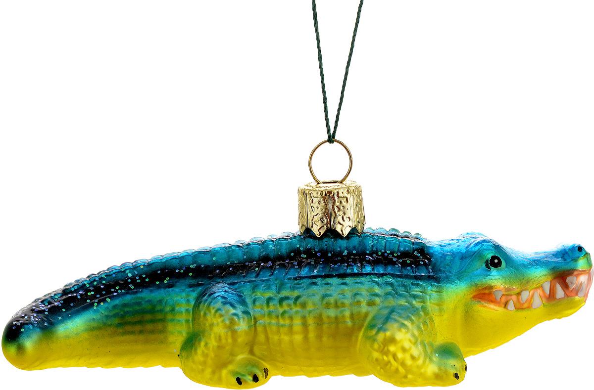 Украшение новогоднее подвесное Winter Wings Крокодил, цвет: синий, желтый, длина 11 смN07222Новогоднее подвесное украшение Winter Wings Крокодил выполнено из стекла в виде крокодила и украшено блестками. С помощью специальной петельки украшение можно повесить в любом понравившемся вам месте. Но, конечно, удачнее всего оно будет смотреться на праздничной елке. Елочная игрушка - символ Нового года. Она несет в себе волшебство и красоту праздника. Создайте в своем доме атмосферу веселья и радости, украшая новогоднюю елку нарядными игрушками, которые будут из года в год накапливать теплоту воспоминаний. Материал: стекло. Длина: 11 см.