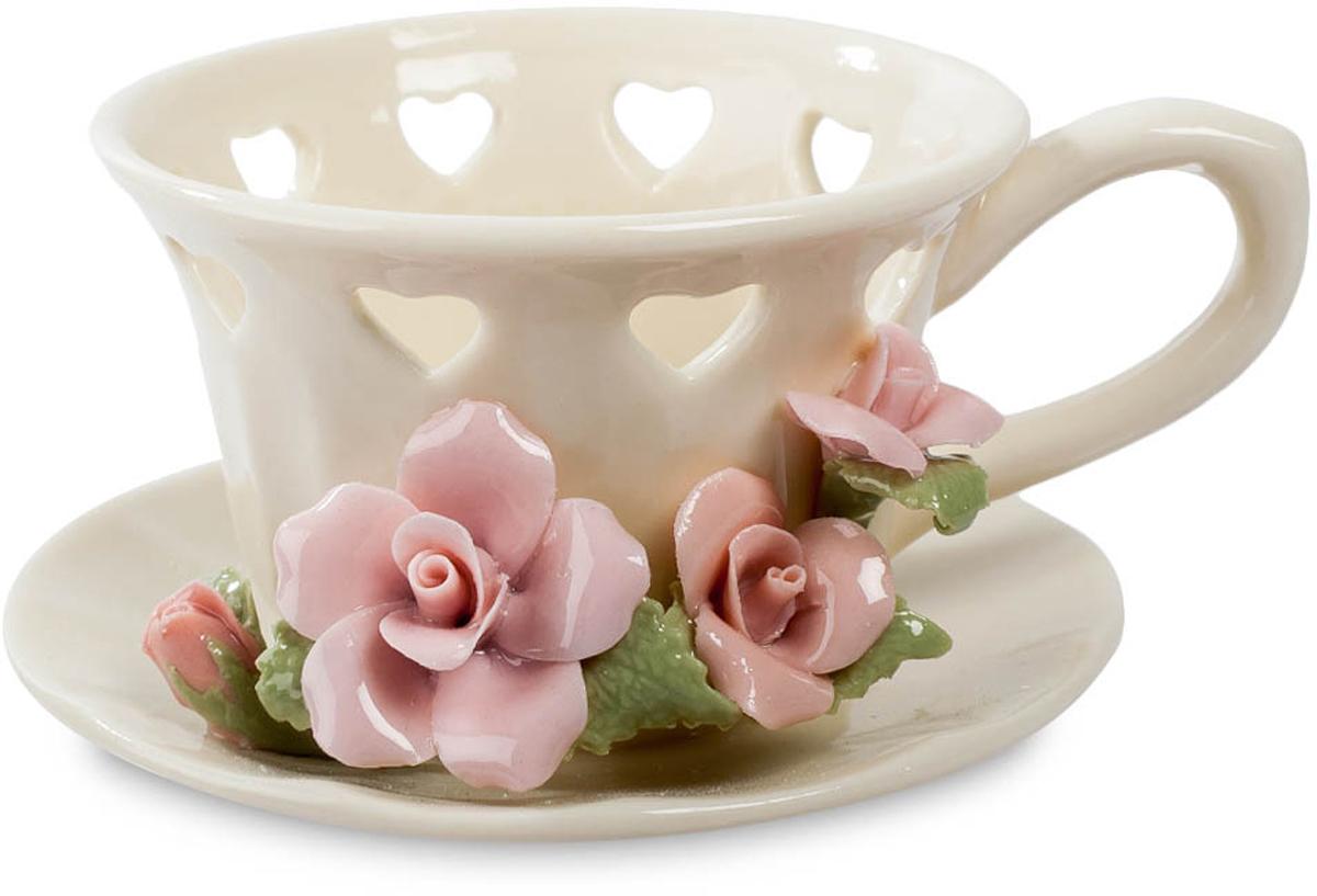 Подсвечник Pavone Чашечка света. CMS-33/33CMS-33/33Подсвечник Чашечка света (Pavone) Обычную чашечку для чая, стоящую на блюдечке, эта композиция напоминает только на первый взгляд. С блюдца эту чашку не снять, розовые цветы, соединяющие две эти детали, очень красивы, но пить чай помешают. Но главное – чашка имеет по периметру множество дырочек, красивых, в форме сердечек, но уж пить из чашки они точно не дадут. Разгадка проста – этот предмет служит для совершенно иной цели: это подсвечник. На дно чашки ставится свеча, и подсвечник удобно брать и переставлять за ручку. Но главный сюрприз ожидает, когда свеча почти догорит, и ее пламя скроется за кромкой чашки. Через каждое отверстие-сердечко проникнет лучик света, озарив пространство вокруг неярким, но волшебным светом. Это будет значить, что интимный ужин при свече достиг своей кульминации и близок к завершению. А что же будет дальше?