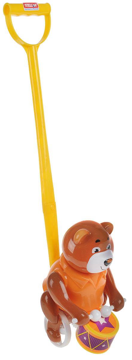 Stellar Игрушка-каталка Барабанщик цвет коричневый оранжевый1377_коричневый, оранжевыйИгрушка-каталка Stellar Барабанщик - симпатичный мишка, который умеет стучать палочками по барабану. Мишка приветливо улыбается, поэтому на его мордочке всегда доброе выражение. Мишка-барабанщик станет хорошим другом для ребенка на прогулке и дома. Дети будут увлеченно бегать, держась за ручку каталки. Чем быстрее будет бегать ваш малыш, тем активнее мишка будет настукивать свои ритмы. Такой забавный барабанщик обязательно понравится всем и подарит замечательное настроение вашим непоседам! Каталка развивает цветовое восприятие, координацию движений, звуко-моторную координацию. Формирует эмоциональную отзывчивость и игровые навыки.