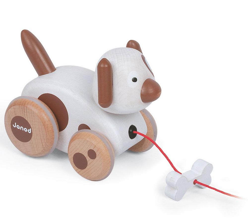 Janod Игрушка-каталка Собачка с колокольчикомJ08117Игрушка-каталка Janod Собачка с колокольчиком изготовлена из дерева. Оригинальный дизайн, и исполнение игрушки на высшем уровне. Погремушка, которая начинает звучать в процессе движения, развлечет ребенка. Такой подарок точно не оставит равнодушным ни одного малыша! Как только малыш делает первые шаги, ему необходимы дополнительные развлечения. Ведь у него очень быстро вспыхивает интерес ко всему, и так же быстро затихает. Но с каталкой на веревочке Собачка с колокольчиком ему определенно никогда не будет скучно!