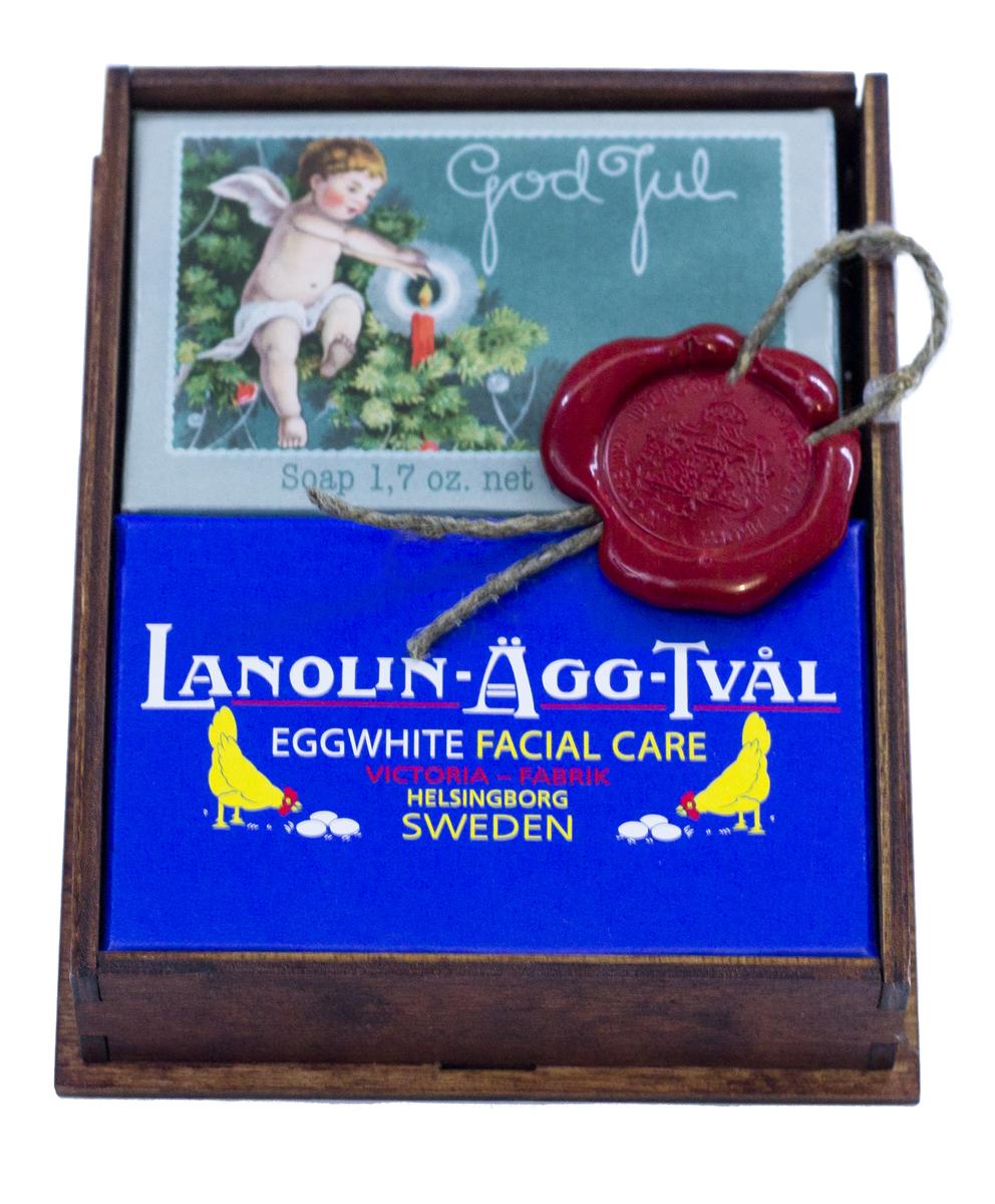 Victoria Soap Малый корф Рождество, арт. 1442411441. Мыло-маска Lanolin-Agg-Tval из яичного белка, созданное по старинному шведскому рецепту, передающееся из поколения в поколение. Уникальное средство превосходно очищает поры от загрязнений, сохраняя ее естественную увлажненность, за счет высокого содержания в нем компонентов натурального происхождения, таких как: ланолин, растительных масел Оливы и масло Ши. А входящий в состав мыло-маски Lanolin-Agg-Tval яичный белок и розовая вода ухаживают за вашей кожей, делая цвет лица более ровным и красивым. Подходит для ежедневного использования, а также в качестве маски для более глубокого очищения 1-2 раза в неделю для всех типов кожи. 2. Мыло-открытка Счастливого Нового Года и Рождества! Очаровательный дизайн коробок напомнит о беззаботном детстве и задорных играх в снежки. А на самом мыле можно найти важное послание от эльфов. Аромат мандарина, корицы и миндаля, ванили, апельсинов и гвоздики окутает Ваш дом волшебством и радостью. 3. Деревянный корф цвета ореха
