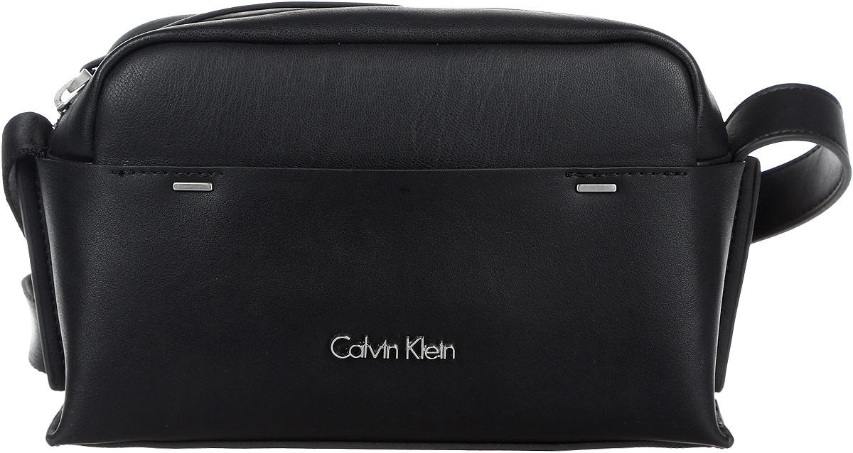 Сумка женская Calvin Klein Jeans, цвет: черный. K60K602424_9100K60K602424_9100Стильная и компактная женская сумка Calvin Klein Jeans выполнена из полиуретана и текстиля. Изделие имеет одно отделение, закрывающееся на застежку-молнию. Внутри находится накладной открытый карман. Снаружи, на передней стенке расположен нашивной открытый карман. Сумка оснащена регулируемым плечевым ремнем. Основание изделия защищено от повреждений металлическими ножками. Стильная сумка идеально подчеркнет ваш неповторимый стиль.