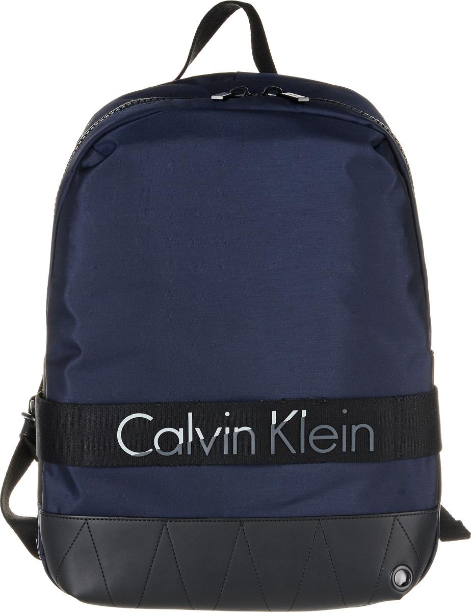 Рюкзак мужской Calvin Klein Jeans, цвет: темно-синий. K50K502293_4380K50K502293_4380Практичный рюкзак Calvin Klein Jeans выполнен из нейлона с добавлением полиуретана и полиэстера. Изделие содержит одно вместительное отделение. Внутри отделения размещены один мягкий карман для планшета, который застегивается хлястиком на липучку, четыре меленьких накладных кармана и один прорезной карман на застежке-молнии. Рюкзак оснащен широкими лямками регулируемой длины и петлей для подвешивания. Дополнена модель надписью с названием бренда.