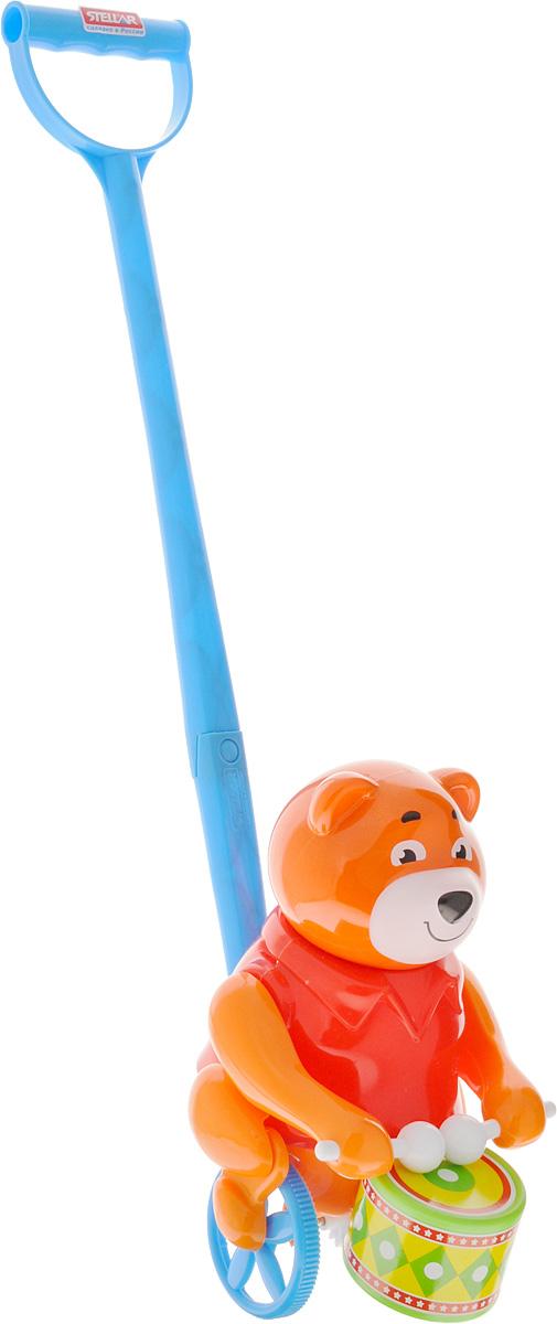 Stellar Игрушка-каталка Барабанщик цвет оранжевый красный1377_оранжевый, красныйИгрушка-каталка Stellar Барабанщик - симпатичный мишка, который умеет стучать палочками по барабану. Мишка приветливо улыбается, поэтому на его мордочке всегда доброе выражение. Мишка-барабанщик станет хорошим другом для ребенка на прогулке и дома. Дети будут увлеченно бегать, держась за ручку каталки. Чем быстрее будет бегать ваш малыш, тем активнее мишка будет настукивать свои ритмы. Такой забавный барабанщик обязательно понравится всем и подарит замечательное настроение вашим непоседам! Каталка развивает цветовое восприятие, координацию движений, звуко-моторную координацию. Формирует эмоциональную отзывчивость и игровые навыки.