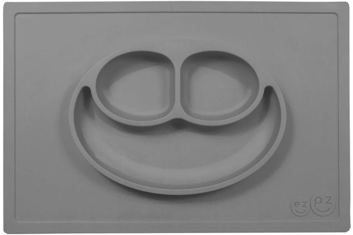 Ezpz Тарелка детская Happy Mat цвет серыйPKHMA005Ezpz Happy Mat - необычная силиконовая тарелка-плейсмат, которая не имеет аналогов. Ее главная особенность заключается в том, что тарелку невозможно перевернуть или опрокинуть. С ней ребенок не сможет испачкать стол или, что гораздо важнее, обжечься горячей пищей. Изготовлена из силикона высочайшего качества и абсолютно безопасна. Не имеет липучек или присосок - фиксация происходит на любой ровной горизонтальной поверхности за счет плоской, гладкой поверхности тарелочки - мата. Подходит для использования в микроволновке и посудомоечной машине. Выглядит как улыбающаяся рожица, что очень нравится детям и их мамам. Тарелка разработана и запатентована в США. Идея создания удобной, безопасной посуды для детей, принадлежит многодетной маме, которая как никто другой знает, как сложно уследить за детками во время еды и сохранить при этом чистоту и порядок. Благодаря такой тарелочке прием пищи становится веселым и безопасным, а кухня остается чистой и опрятной. Объем 540 мл.