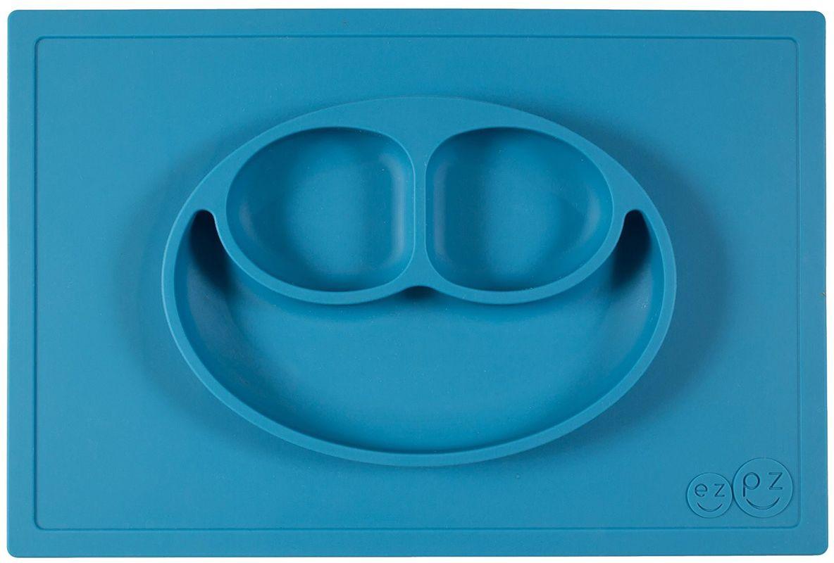Ezpz Тарелка детская Happy Mat цвет голубойPKHMB003Ezpz Happy Mat - необычная силиконовая тарелка-плейсмат, которая не имеет аналогов. Ее главная особенность заключается в том, что тарелку невозможно перевернуть или опрокинуть. С ней ребенок не сможет испачкать стол или, что гораздо важнее, обжечься горячей пищей. Изготовлена из силикона высочайшего качества и абсолютно безопасна. Не имеет липучек или присосок - фиксация происходит на любой ровной горизонтальной поверхности за счет плоской, гладкой поверхности тарелочки - мата. Подходит для использования в микроволновке и посудомоечной машине. Выглядит как улыбающаяся рожица, что очень нравится детям и их мамам. Тарелка разработана и запатентована в США. Идея создания удобной, безопасной посуды для детей, принадлежит многодетной маме, которая как никто другой знает, как сложно уследить за детками во время еды и сохранить при этом чистоту и порядок. Благодаря такой тарелочке прием пищи становится веселым и безопасным, а кухня остается...