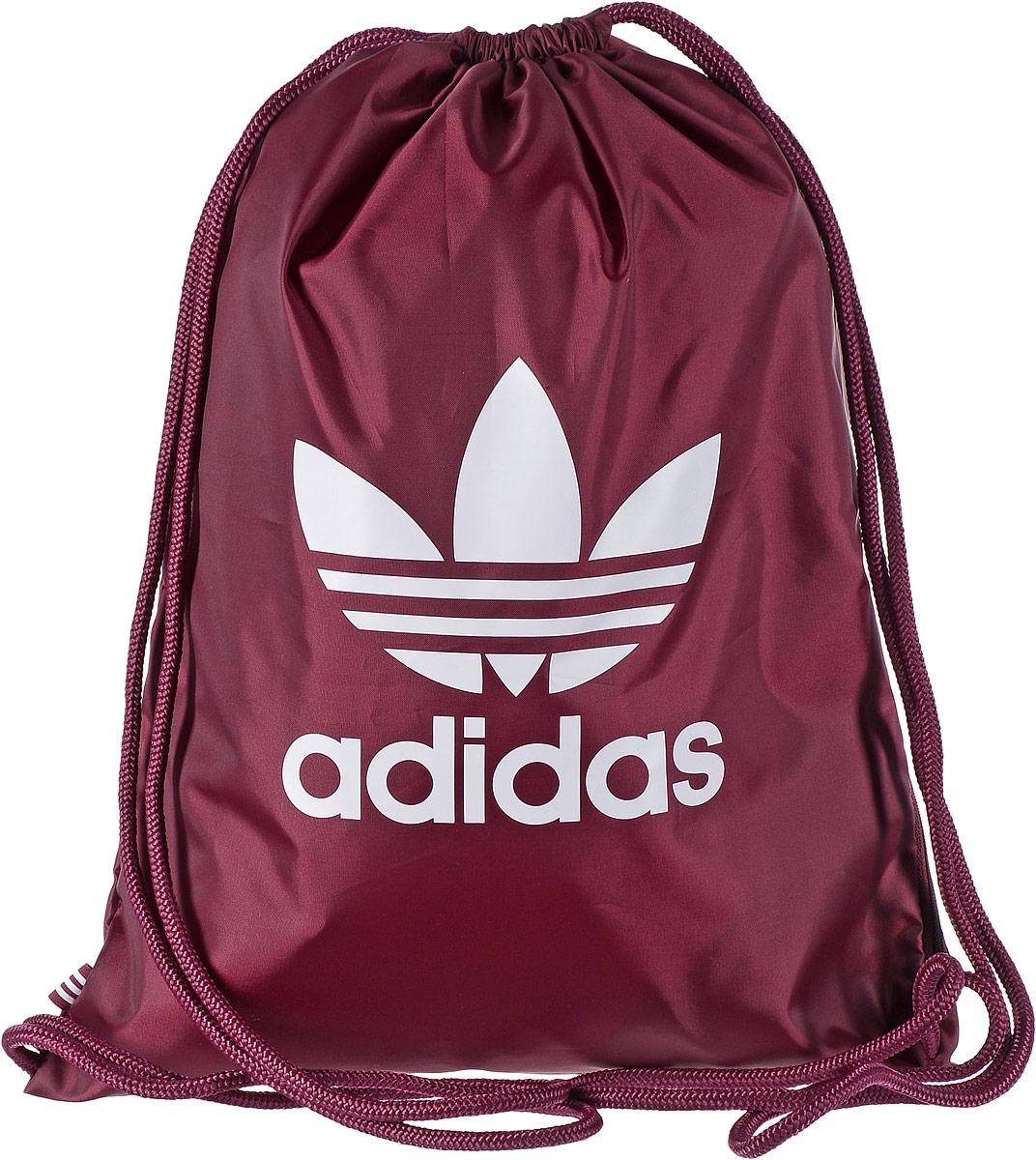 Рюкзак спортивный Adidas Trefoil, цвет: бордовый, 23 л. BK6728BK6728Стильный спортивный рюкзак Adidas Trefoil выполнен из полиэстера и оформлен символикой бренда. Изделие имеет одно основное отделение, которое закрывается с помощью затягивающего шнурка. С внутренней стороны изделие оснащено удобной ручкой для переноски. Снаружи, с одной из боковых сторон находится прорезной карман на застежке-молнии. Веревочные завязки можно использовать как наплечные лямки. Стильный и функциональный рюкзак поместит все необходимое.