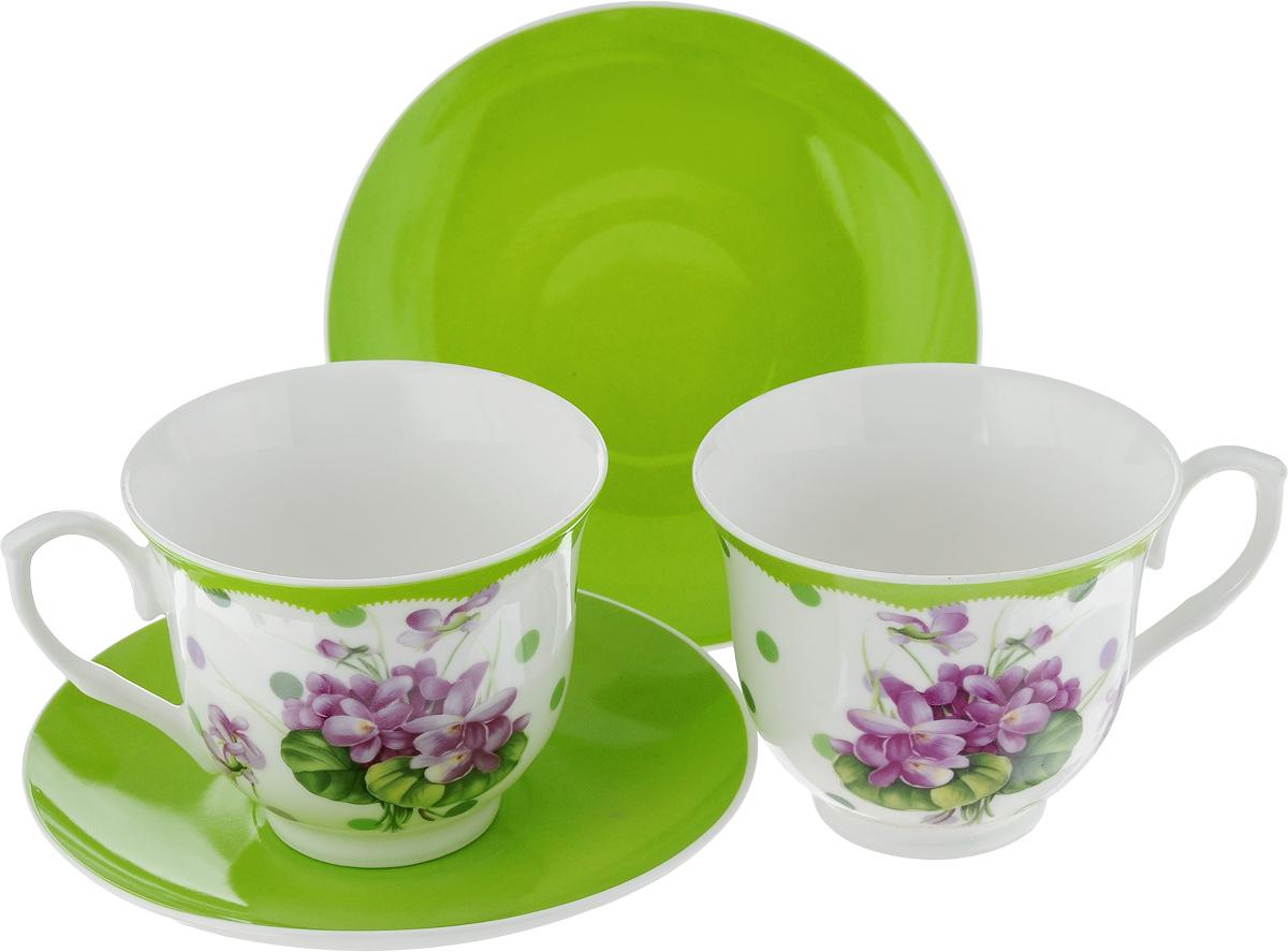 Набор чайный Loraine Лютик, цвет: белый, фиолетовый, зеленый, 4 предмета22992Чайный набор Loraine Лютик, выполненный из керамики, состоит из 2 чашек и 2 блюдец. Предметы набора имеют яркую расцветку. Изящный дизайн и красочность оформления придутся по вкусу и ценителям классики, и тем, кто предпочитает современный стиль. Чайный набор - идеальный и необходимый подарок для вашего дома и для ваших друзей в праздники, юбилеи и торжества! Он также станет отличным корпоративным подарком и украшением любой кухни. Чайный набор упакован в подарочную коробку из плотного цветного картона. Внутренняя часть коробки задрапирована белым атласом. Диаметр кружки (по верхнему краю): 9 см. Высота стенки: 7,5 см. Диаметр блюдца: 14,2 см. Высота блюдца: 2 см. Объем чашки: 220 см.
