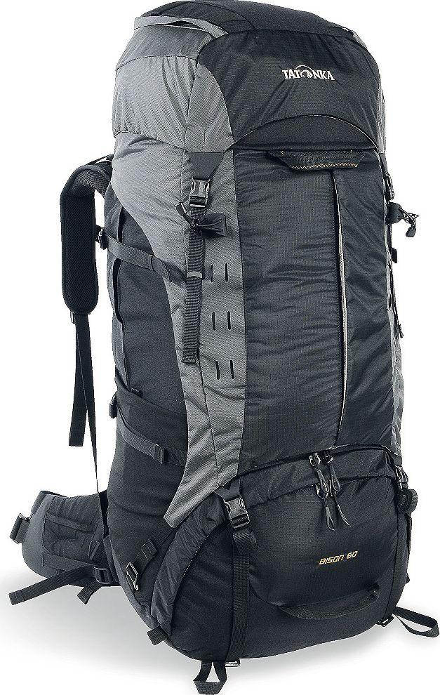 Рюкзак туристический Tatonka Bison, цвет: черный, 90+10 л1357.040Туристический рюкзак Tatonka Bison 90 - лучший выбор для тех, кто отправляется в длительный пеший поход c грузом, вес которого 25-35 килограмм. Благодаря системе подвески Х1, до 85% веса переносимого груза рюкзак перераспределит с плеч на бедра, тем самым спасая вашу спину и плечи от боли и усталости. Особенности рюкзака Tatonka Bison 90 Внешний вид В 2017 году Tatonka обновила дизайн и материалы рюкзака, благодаря чему он стал легче и современнее. Рюкзак выполнен из прочных материалов Cordura 500D, T-Square Rip и T-Snow Crust. Cordura с толщиной волокна 500 ден сочетает высокую прочность на разрыв и истирание классического волокна 1000 ден с легкостью материала 500 ден. Она делает рюкзак чрезвычайно прочным и износостойким. T-Square Rip и T-Snow Crust - лёгкие и прочные материалы, которые помогают снизить вес рюкзака. Система Х1 состоит из двух эргономично изогнутых X-образно скрещенных шин и полиэтиленовой пластины, необходимой для...