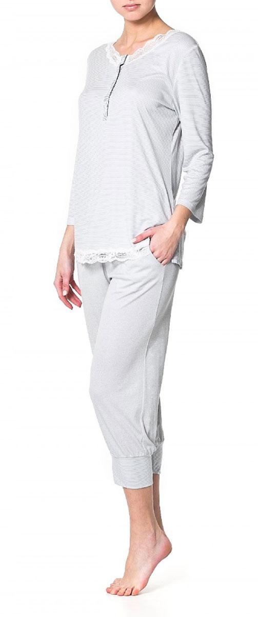 R1550-41Пижамная блузка Ardi, выполненная из вискозы с модалом, очень мягкая на ощупь и приятная к телу. Модель прямого кроя с круглым воротником и рукавами 3/4 оформлена оригинальным принтом в мелкую полоску. Горловина и низ блузки украшены узкой кружевной тесьмой. Спереди имеется планка из отделочной ткани до уровня груди с петлями и пуговицами.