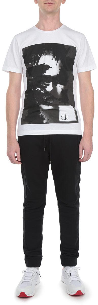Брюки спортивныеR2541-92Мужские спортивные брюки Calvin Klein Jeans станут отличным дополнением к вашему гардеробу. Изготовленные из натурального хлопка, они мягкие и приятные на ощупь, не сковывают движения и позволяют коже дышать, обеспечивая комфорт. Лицевая сторона изделия гладкая, изнаночная с небольшими петельками. Брюки на поясе имеют широкую трикотажную резинку, регулируемую скрытым шнурком. Спереди предусмотрены два прорезных кармана на молнии, сзади - один. Имеется имитация ширинки. Снизу брючины дополнены широкими эластичными манжетами. Сбоку изделие оформлено объемной надписью с названием бренда, а также декорировано сзади небольшой металлической пластиной с фирменным логотипом. Брюки идеально подойдут для повседневной носки, а также для активного отдыха или занятия спортом.