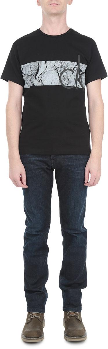 J3IJ302666Стильная мужская футболка Calvin Klein Jeans, выполненная из мягкого хлопка, обладает высокой теплопроводностью, воздухопроницаемостью и гигроскопичностью, позволяет коже дышать. Модель с короткими рукавами и круглым вырезом горловины - идеальный вариант для создания образа в стиле Casual. Футболка спереди оформлена оригинальным принтом и логотипом бренда. Такая модель подарит вам комфорт в течение всего дня и послужит замечательным дополнением к вашему гардеробу.