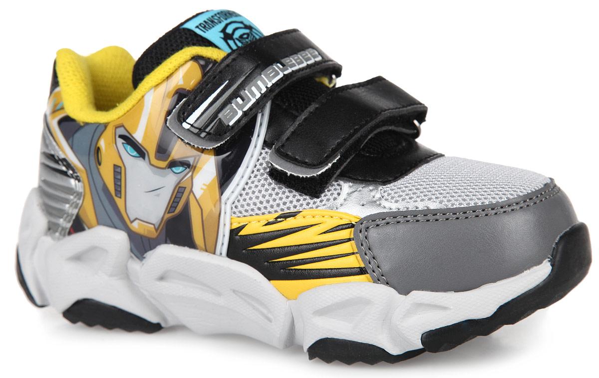 Кроссовки для мальчика Transformers. 52545254BСтильные кроссовки Transformers от Kakadu заинтересуют вашего малыша с первого взгляда! Модель выполнена из комбинации синтетической кожи и сетчатого текстиля. Подъем оформлен ремешками на застежке-липучке, которые надежно зафиксируют модель на ножке. Благодаря такой застежке ребенок может самостоятельно надевать обувь. Подкладка выполнена из 100% гипоаллергенного хлопка - материала, который позволяет коже дышать и хорошо впитывает влагу. Мягкая, амортизирующая, антибактериальная стелька из EVA-материала с текстильной поверхностью обладает высокой воздухопроницаемостью, нейтрализует неприятный запах и препятствует появлению бактерий. Задник дополнен принтом в виде символики бренда, ремешок - оригинальным тиснением, язычок - текстильной нашивкой. Подошва, изготовленная из EVA-материала и термопластичной резины, оснащена рифлением для лучшей сцепки с поверхностью. При движении расположенная сбоку нашивка с изображением трансформера начинает светиться, благодаря чему ваш ребенок...