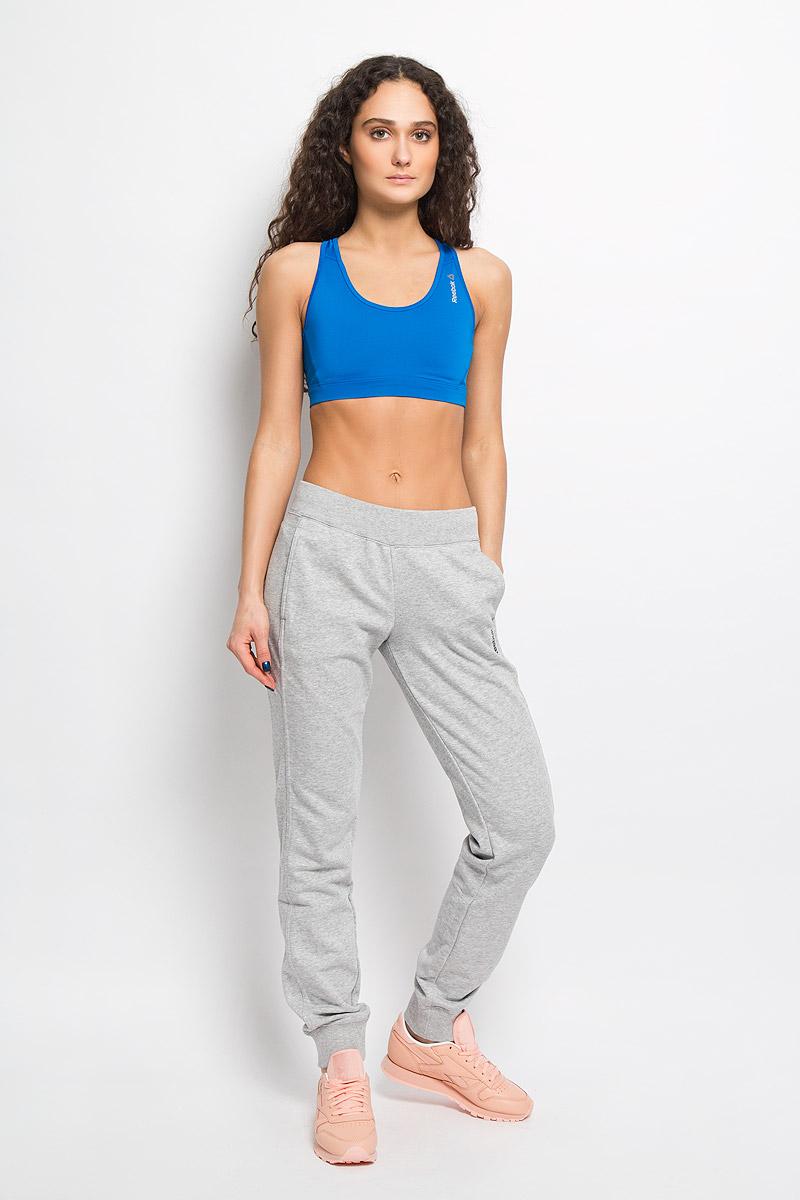 Брюки спортивныеAB0152Удобные женские спортивные брюки Reebok EL FT C великолепно подойдут для отдыха и занятий спортом. Изготовленные из высококачественного материала, они необычайно мягкие и легкие. Модель дополнена широкими эластичными резинками на поясе и понизу брючин. Объем талии регулируется с внутренней стороны при помощи шнурка-кулиски. Спереди предусмотрены два втачных кармана. Оформлено изделие небольшой термоаппликацией в виде названия бренда. Эти модные и в то же время удобные брюки - настоящее воплощение комфорта. В них вы всегда будете чувствовать себя уверенно и уютно.