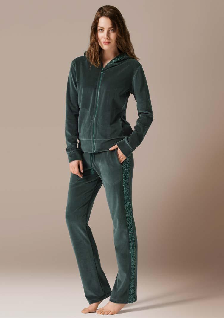 Комплект женский: толстовка, брюки. 7145271452Комплект домашней одежды CatherineS, состоящий из толстовки и брюк, станет отличным дополнением к вашему гардеробу. Изделия выполнены из приятного на ощупь велюра. Толстовка свободного силуэта с капюшоном застегивается на молнию. Спереди расположены втачные карманы. Рукава с широкими манжетами. Капюшон по канту оформлен пайетками. Прямые свободные брюки на широкой эластичной резинке с завязками - удобная и практичная вещь в гардеробе. По бокам расположены втачные карманы. Модель оформлена пайетками. Домашняя одежда играет большую роль в гардеробе женщины, ведь каждой женщине хочется даже дома выглядеть привлекательной.