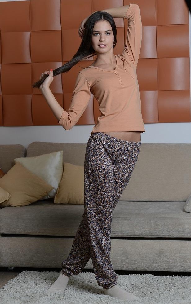 Домашний комплект8006Женский домашний костюм Alla Buone состоит из лонгслива и брюк. Лонгслив с V-образным вырезом горловины и рукавами 3/4, изготовленный из эластичного хлопка, оформлен спереди декоративными пуговицами и дополнен нагрудным накладным карманом. Брюки из натурального хлопка с эластичным поясом оформлены оригинальным принтом. Низ брюк присборен на резинки.