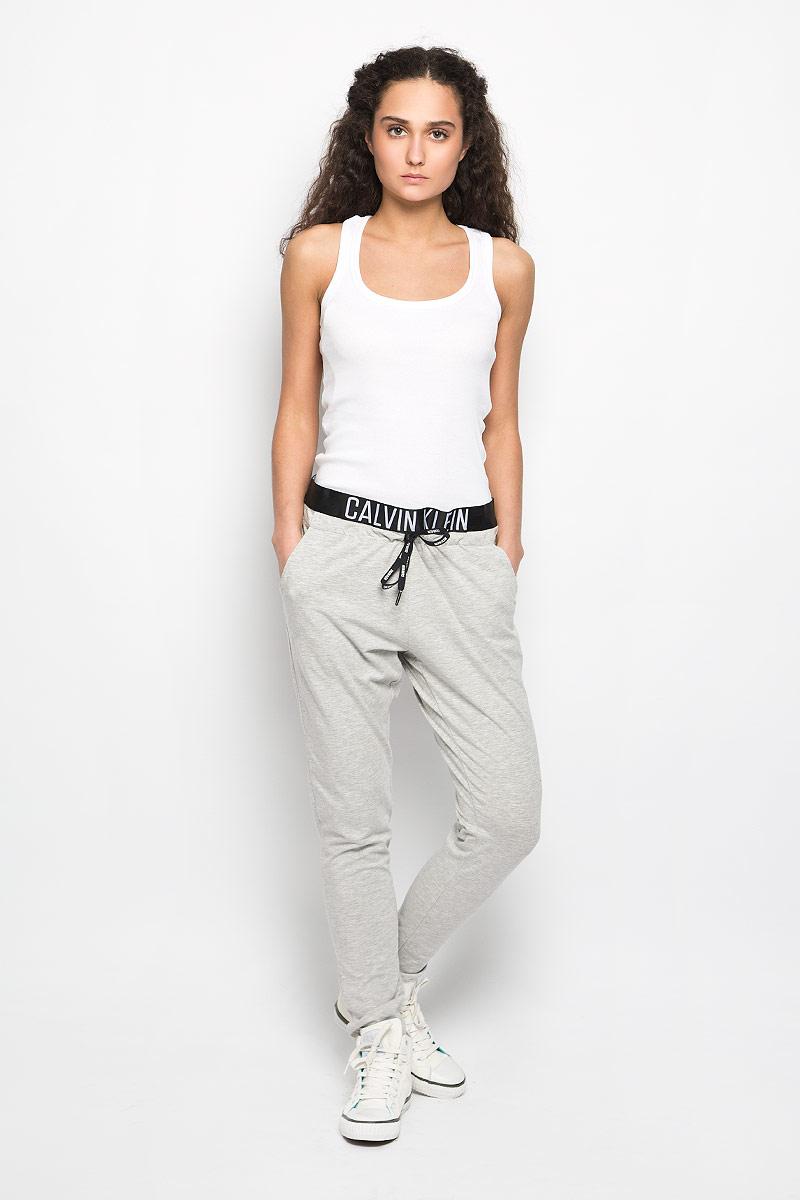 Брюки спортивные женские. K9WK011076K9WK011076_050Женские спортивные брюки Calvin Klein, изготовленные из хлопка и модала с добавлением эластана, идеально подходят как для активного отдыха, так и для неспешных прогулок. Современный дизайн, созданный специально для девушек, которые ценят стиль. Модель зауженного кроя и средней посадки обеспечивает комфорт во время занятий спортом. Эластичный пояс, оформленный названием бренда, гарантирует отличную посадку модели. Обхват талии регулируется с помощью затягивающегося шнурка. Спереди модель дополнена двумя втачными карманами. Такая модель станет стильным дополнением к вашему гардеробу и подарит вам комфорт в течение всего дня!
