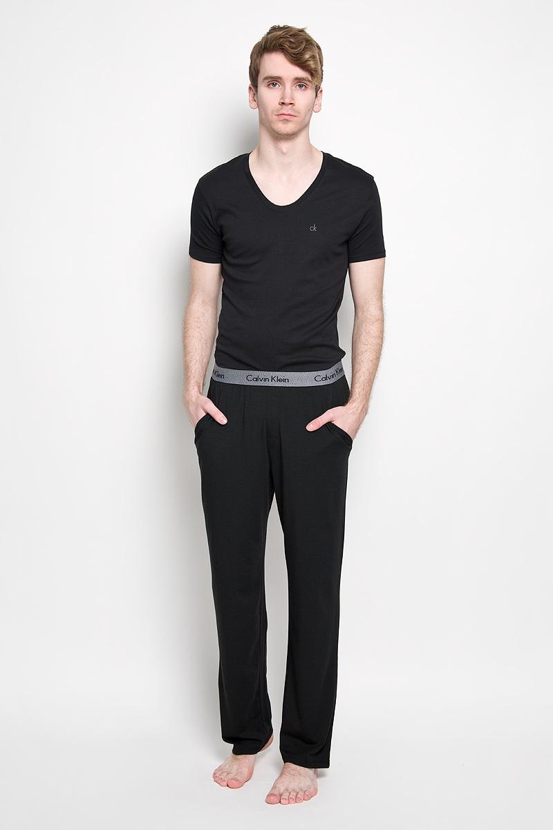 Брюки пижамные мужские. NM1073ANM1073A_001Мужские пижамные брюки Calvin Klein, выполненные из хлопка с добавлением модала и эластана, легкие и приятные к телу, отлично пропускают воздух. Модель прямого кроя имеет на талии широкую резинку, оформленную надписями с названием бренда. Спереди изделие дополнено двумя втачными карманами с косыми срезами. Такие брюки станут идеальным дополнением к вашему гардеробу, в них вы будете чувствовать себя комфортно и уютно!