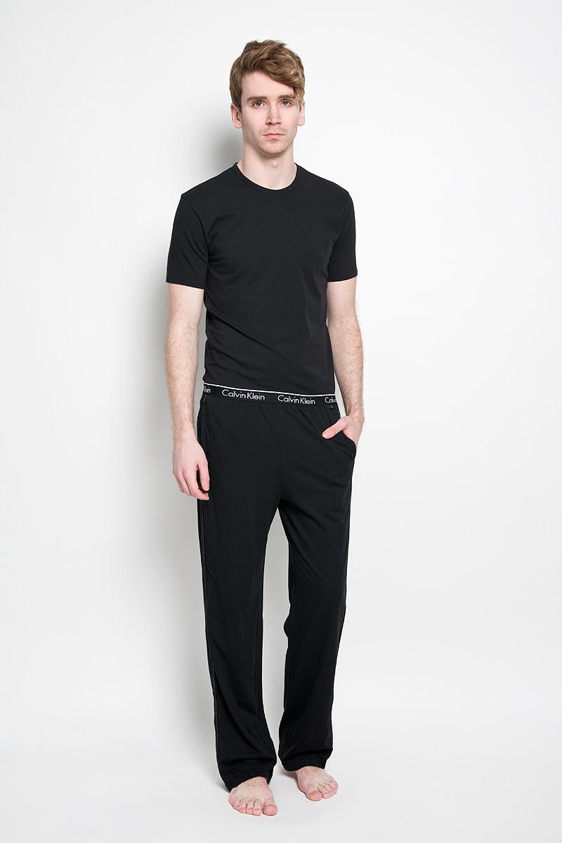 Брюки для домаU8507A_001Мужские пижамные брюки Calvin Klein, выполненные из натурального хлопка, легкие, приятные к телу, отлично пропускают воздух. Модель прямого кроя имеет на талии широкую резинку, оформленную надписями с названием бренда. Спереди изделие дополнено двумя втачными карманами. Боковые швы декорированы тонкими лампасами с названием бренда. Такие брюки станут идеальным дополнением к вашему гардеробу, в них вы будете чувствовать себя комфортно и уютно!
